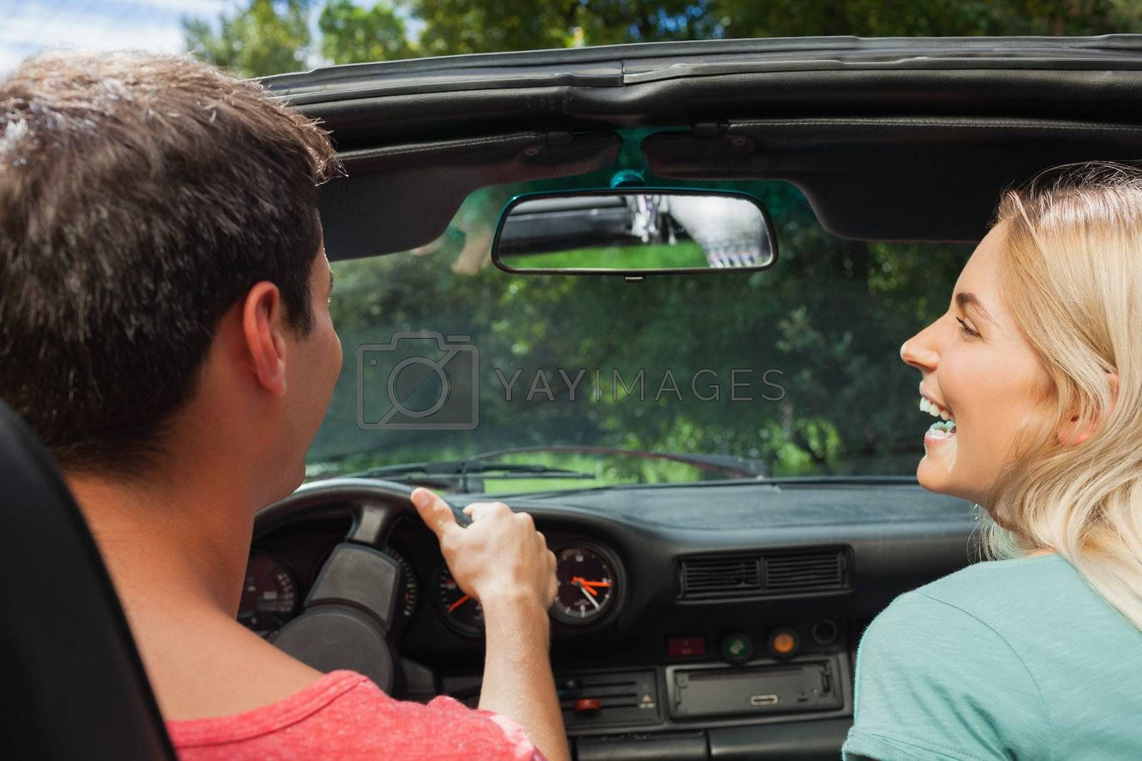 Rear view of smiling couple in cabriolet by Wavebreakmedia
