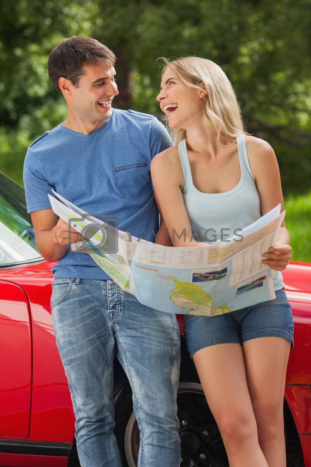 Smiling young couple reading map by Wavebreakmedia