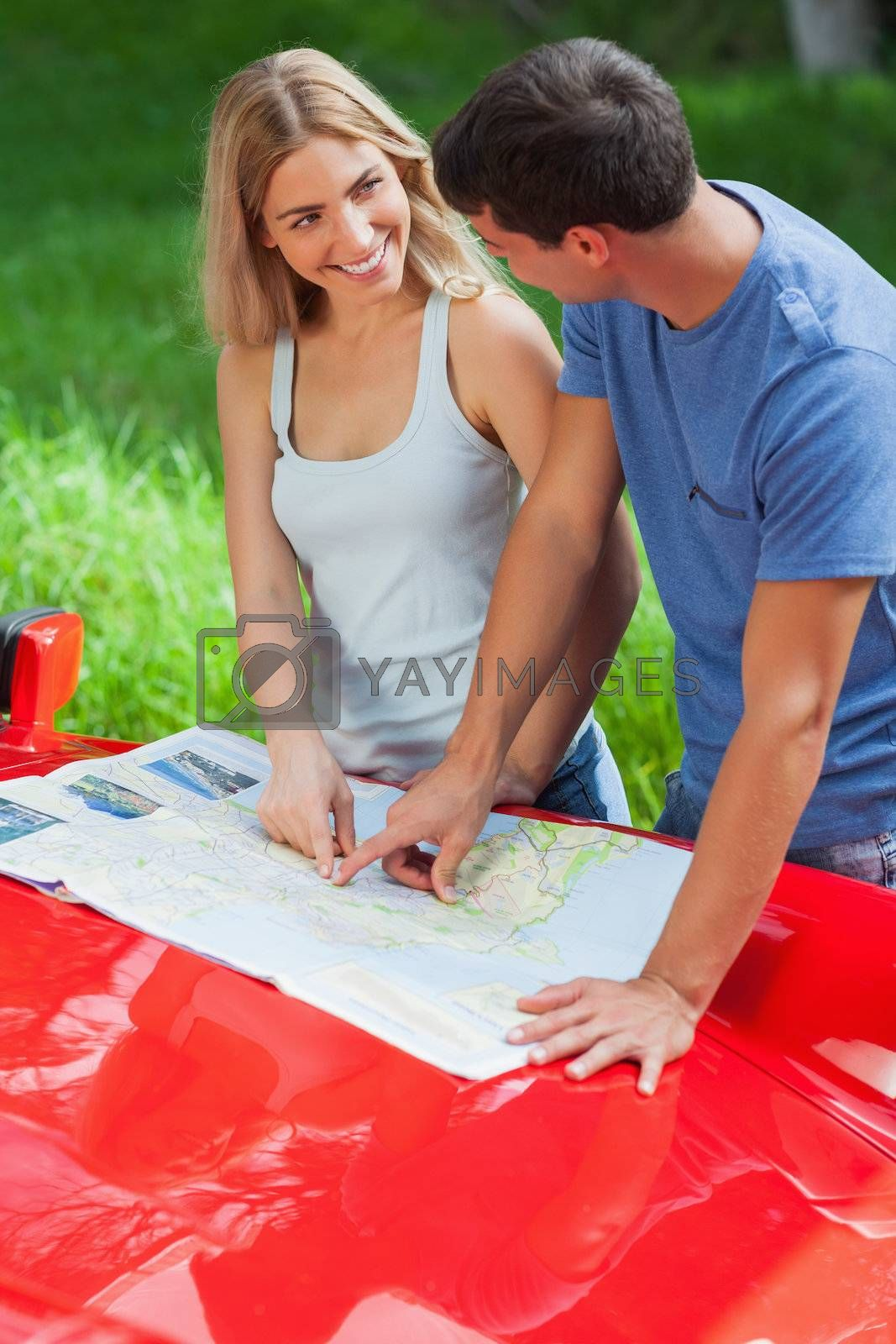Smiling young couple reading map on their cabriolet bonnet by Wavebreakmedia