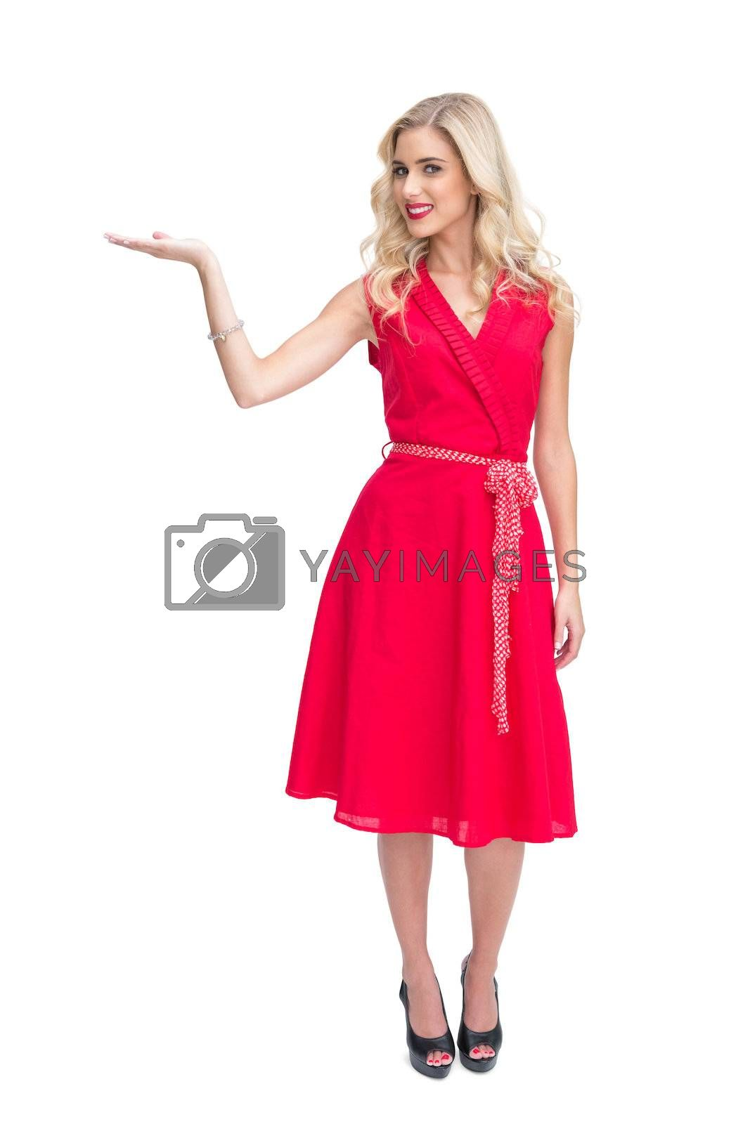 Cheerful woman in red dress presenting something in her hand by Wavebreakmedia