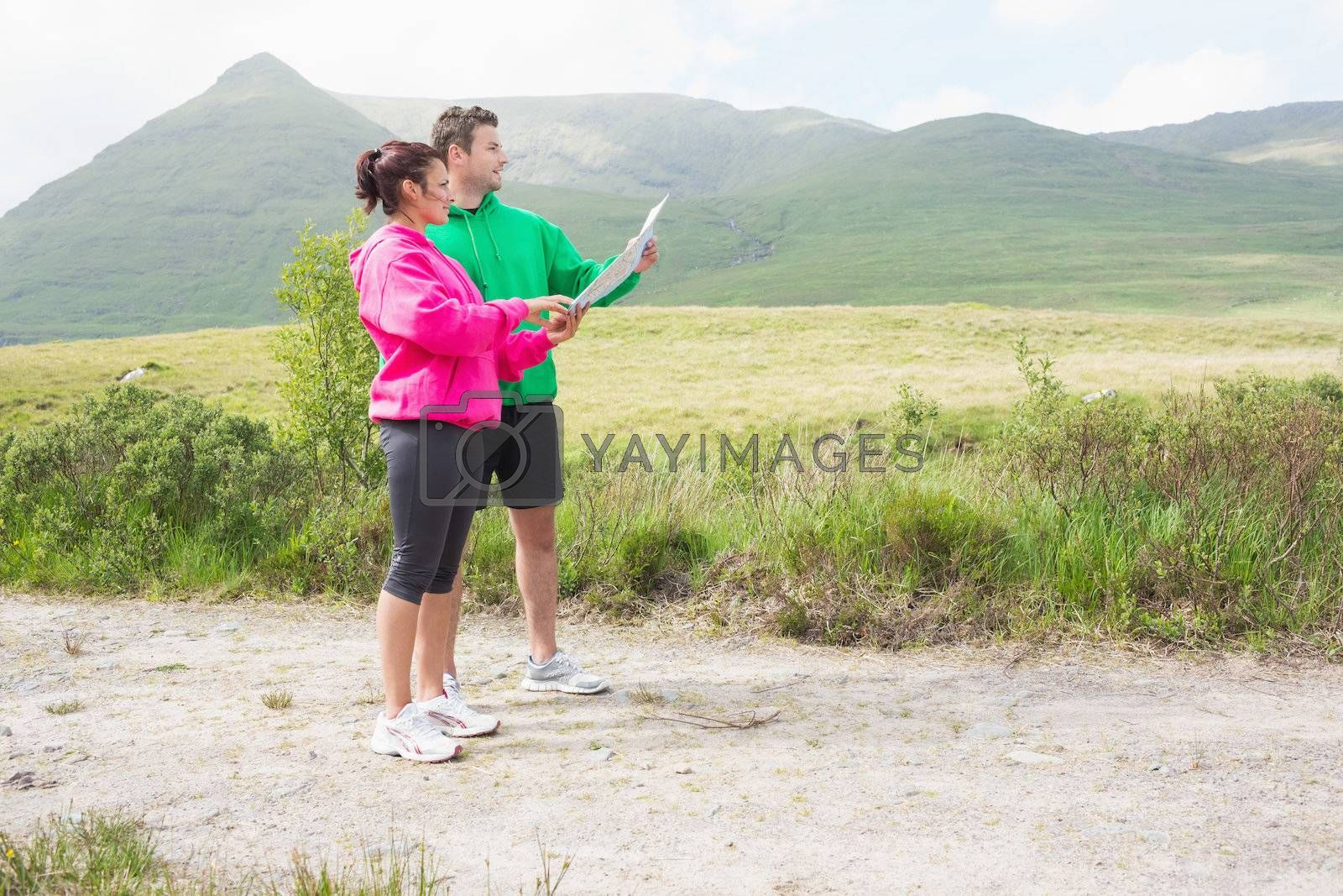 Athletic couple holding a map and looking ahead by Wavebreakmedia