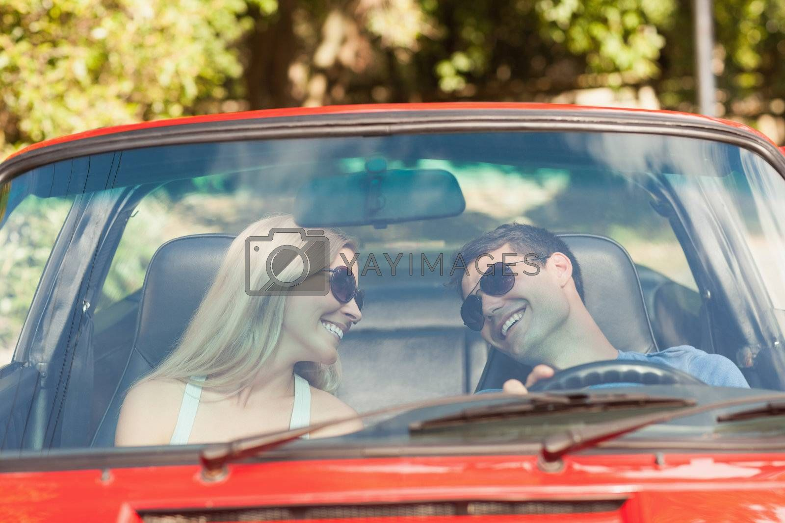 Loving couple in their red cabriolet having a ride by Wavebreakmedia
