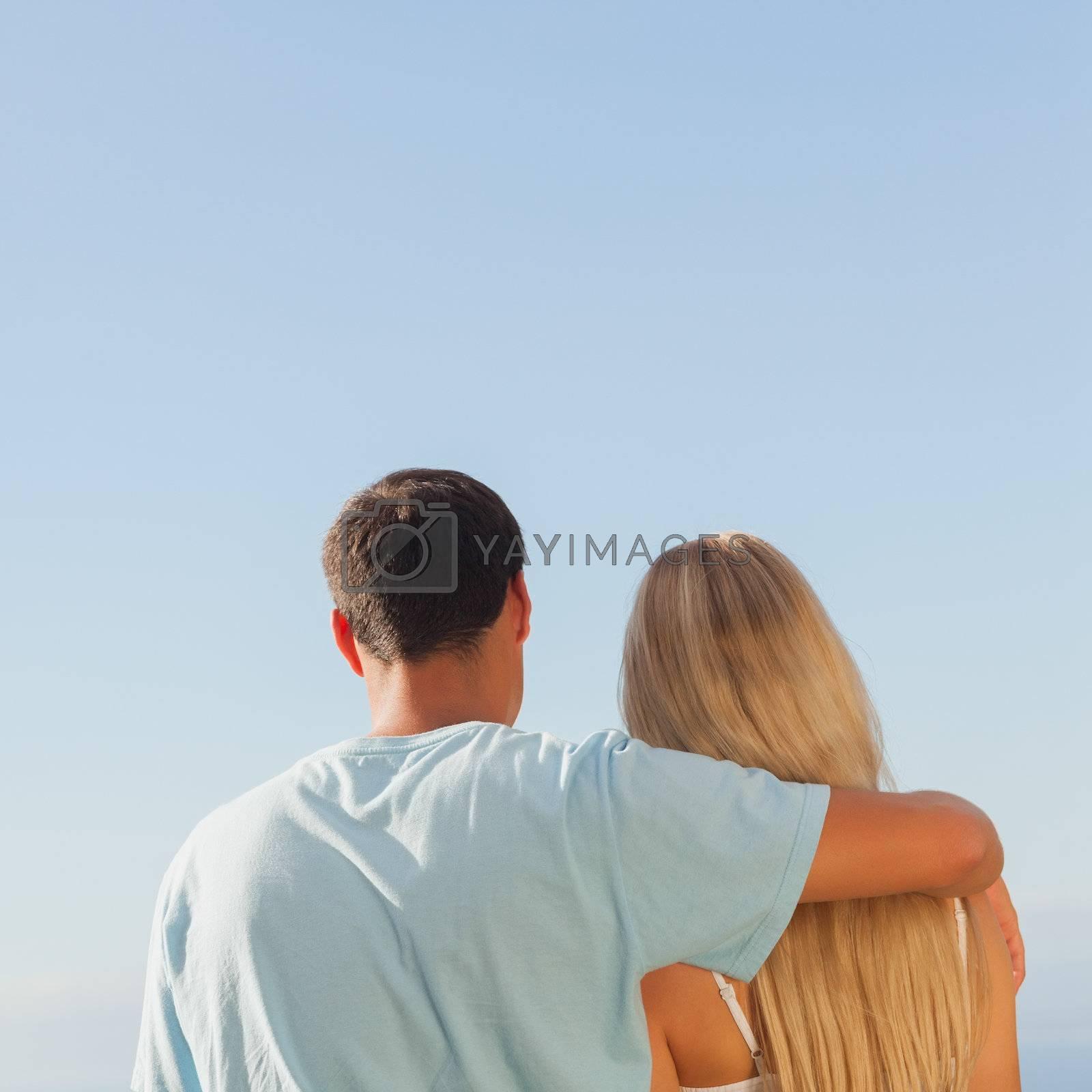Rear view of cute couple admiring blue sky by Wavebreakmedia