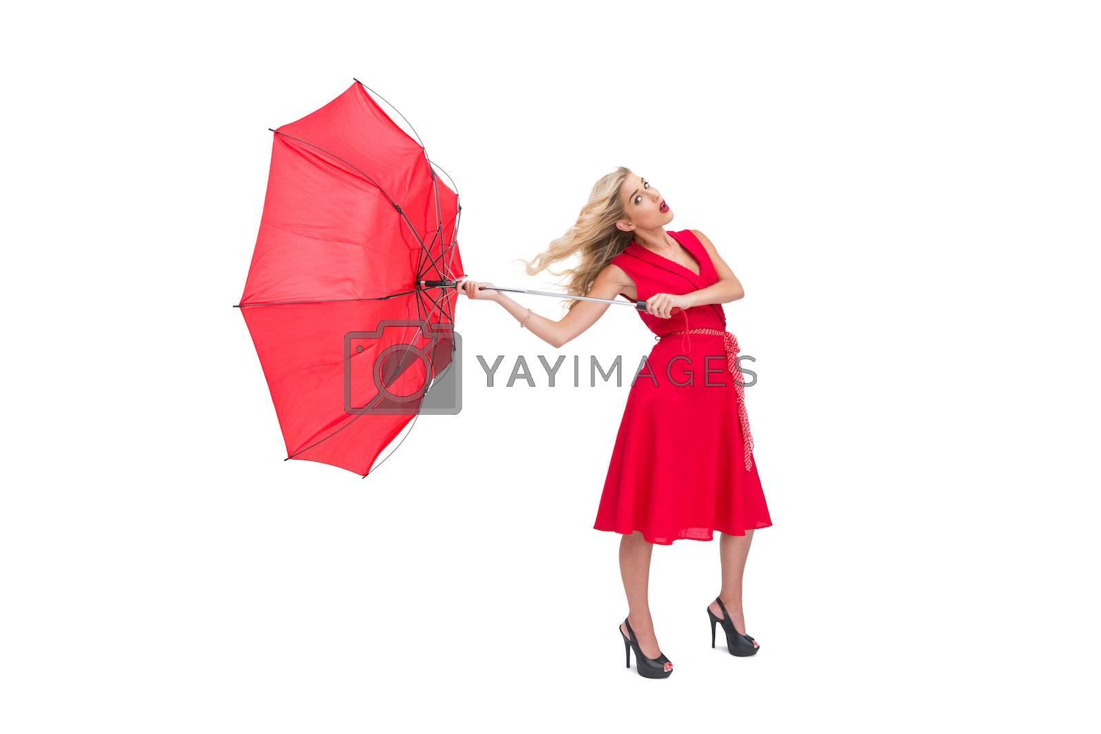 Attractive glamour woman holding a broken umbrella by Wavebreakmedia