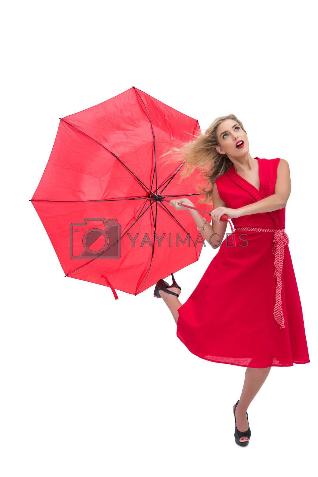 Beautiful woman wearing red dress holding umbrella  by Wavebreakmedia