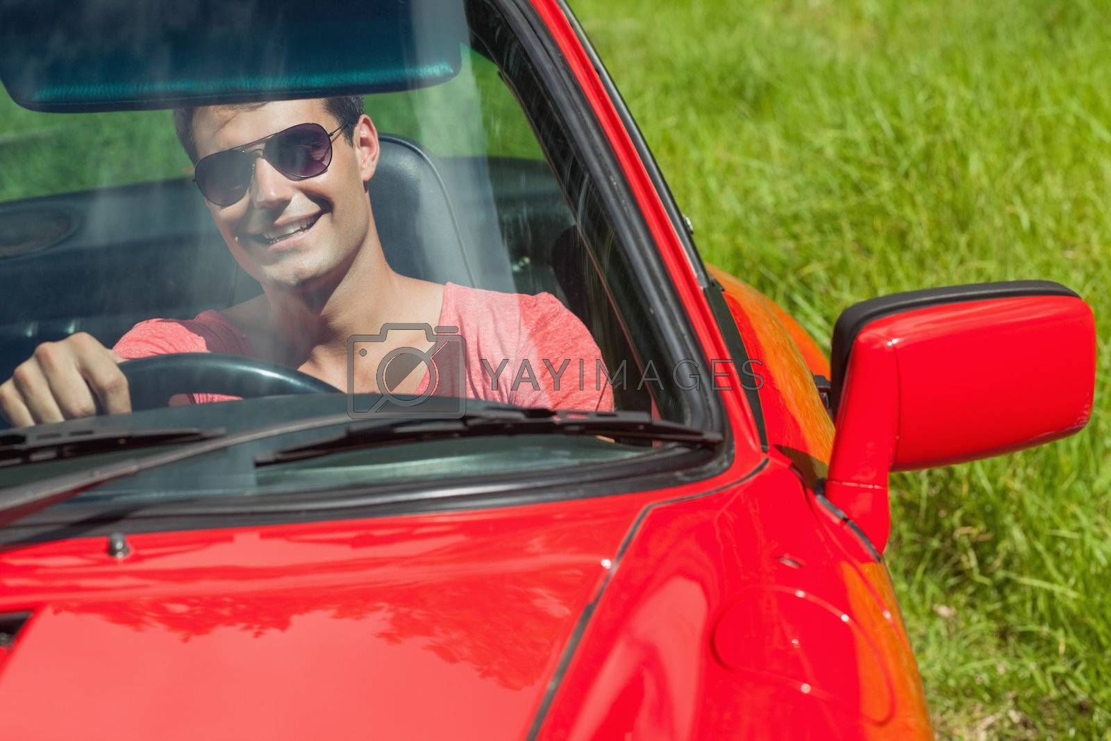 Smiling handsome man driving his cabriolet by Wavebreakmedia