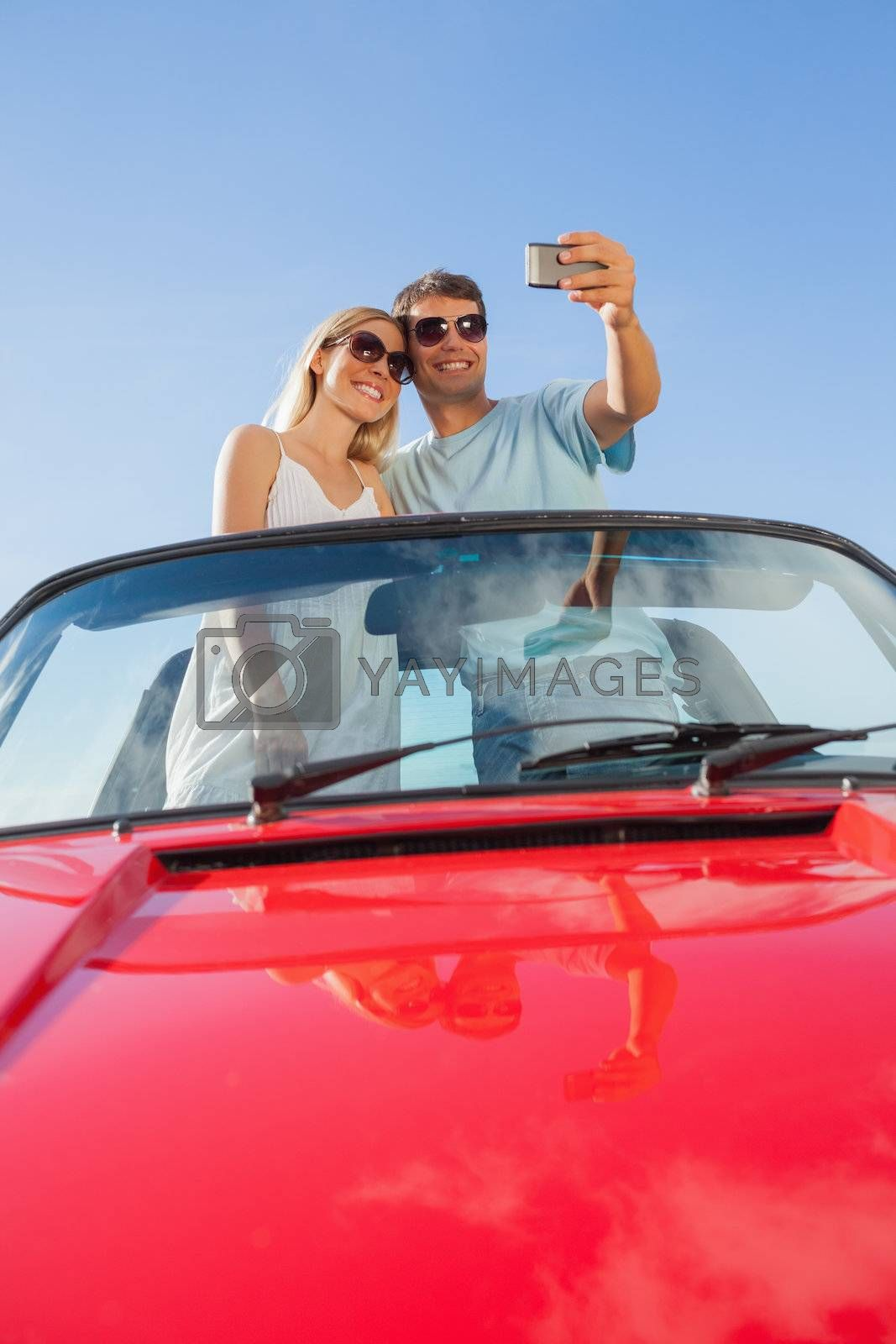 Smiling couple standing in red cabriolet taking picture by Wavebreakmedia