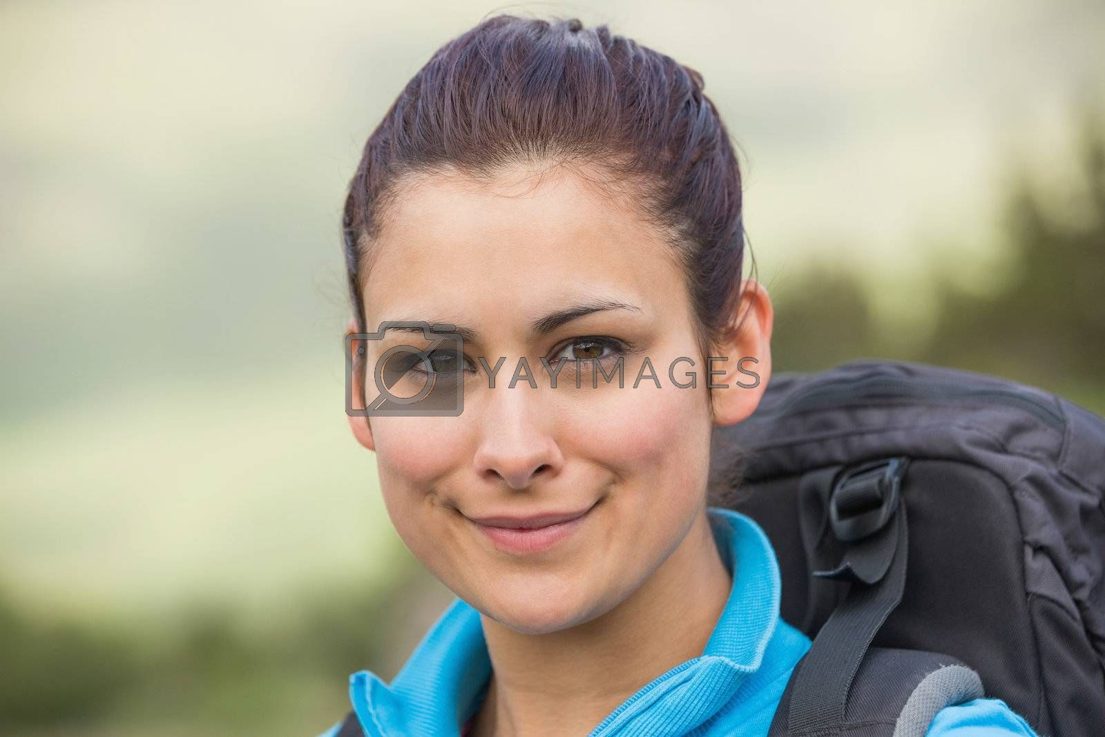 Female hiker with backpack smiling at camera by Wavebreakmedia