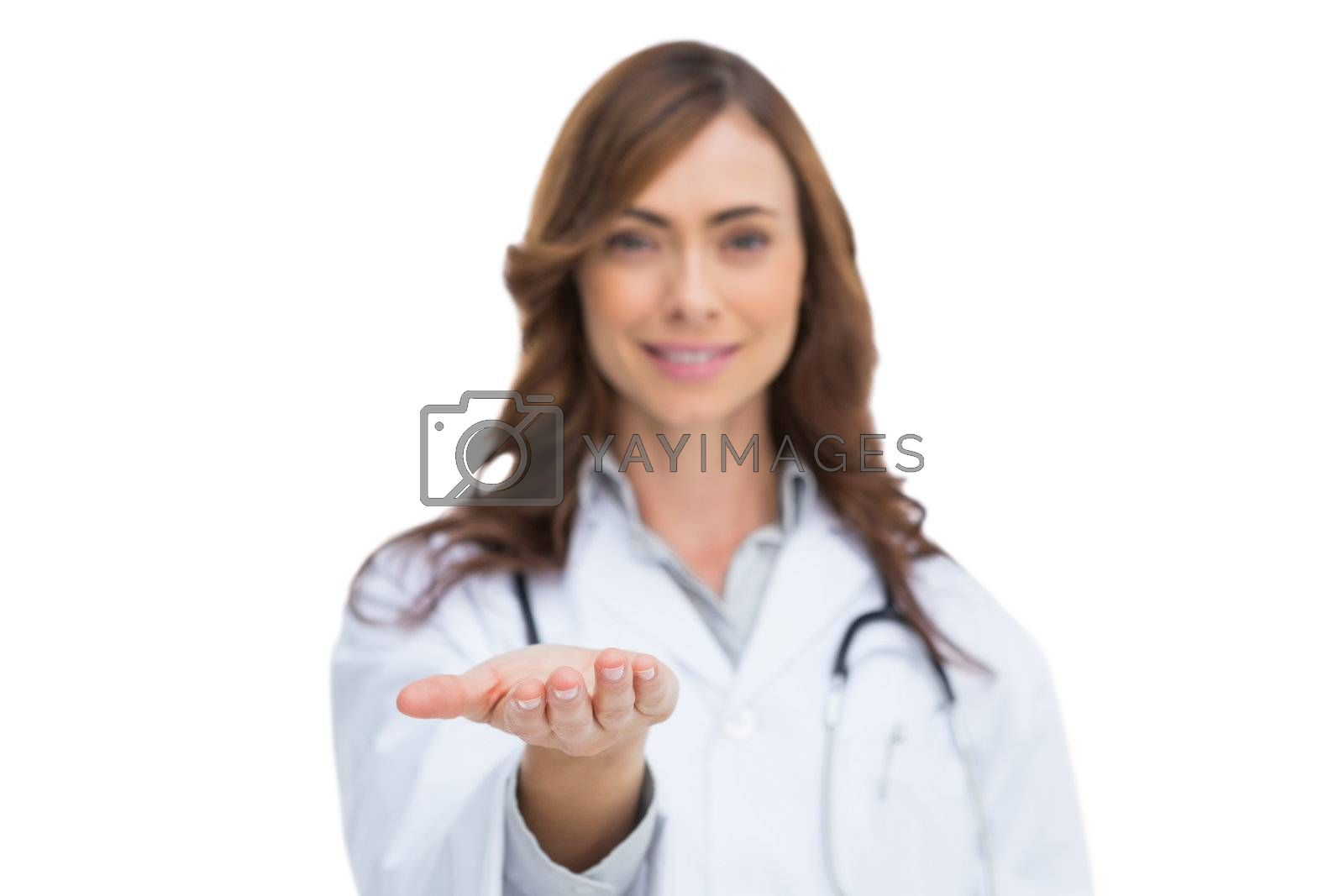 Smiling doctor showing something in her hand by Wavebreakmedia