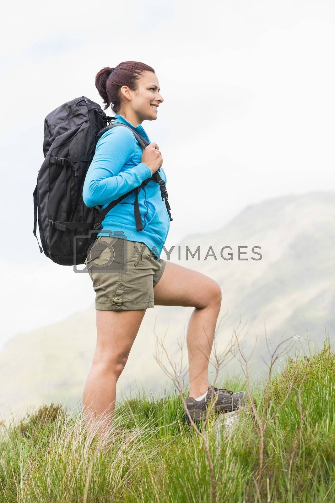 Attractive hiker with backpack walking uphill by Wavebreakmedia