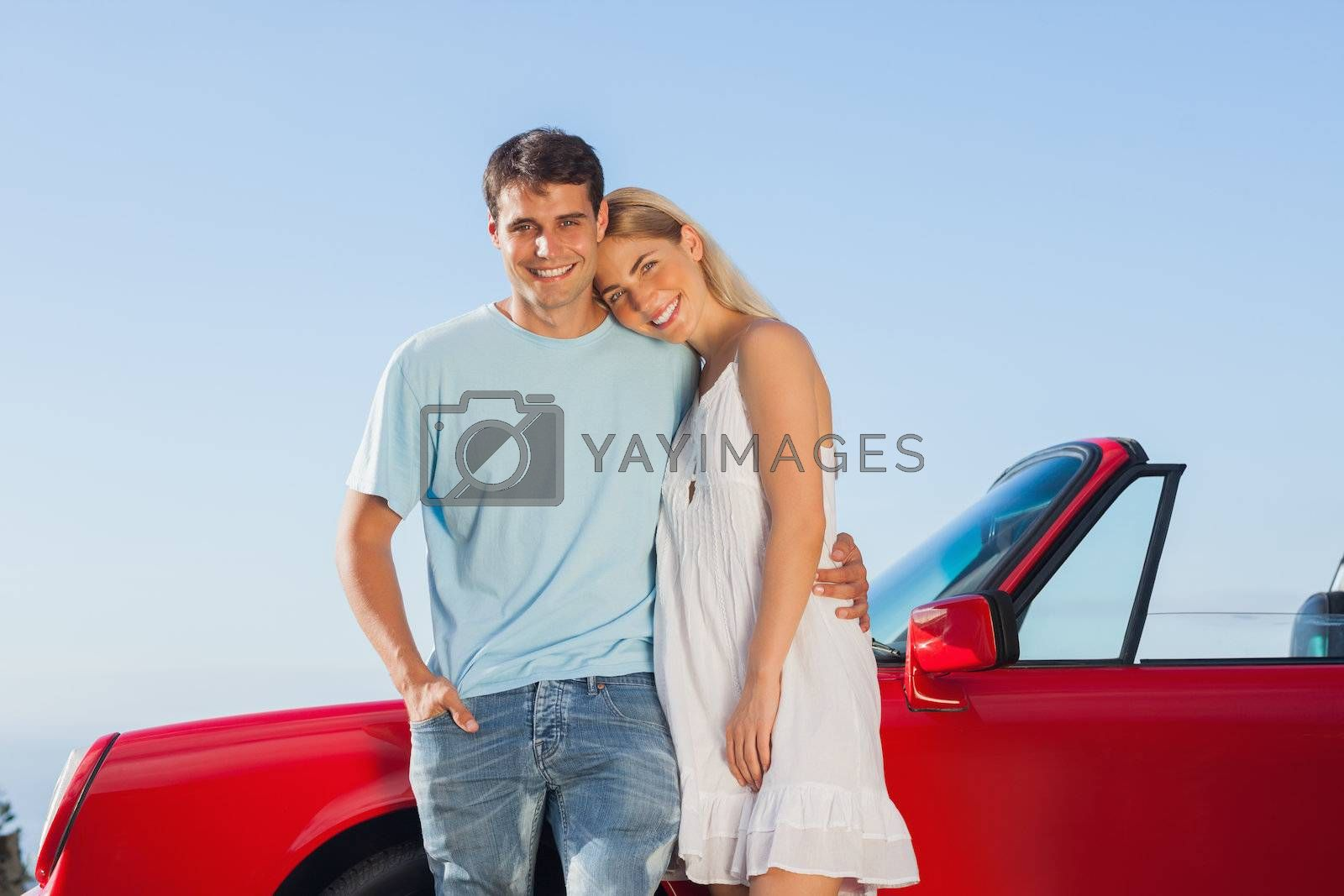 Smiling cute couple posing against their red cabriolet by Wavebreakmedia