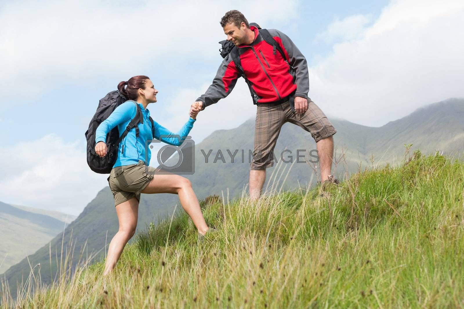 Attractive hiker helping his girlfriend uphill by Wavebreakmedia