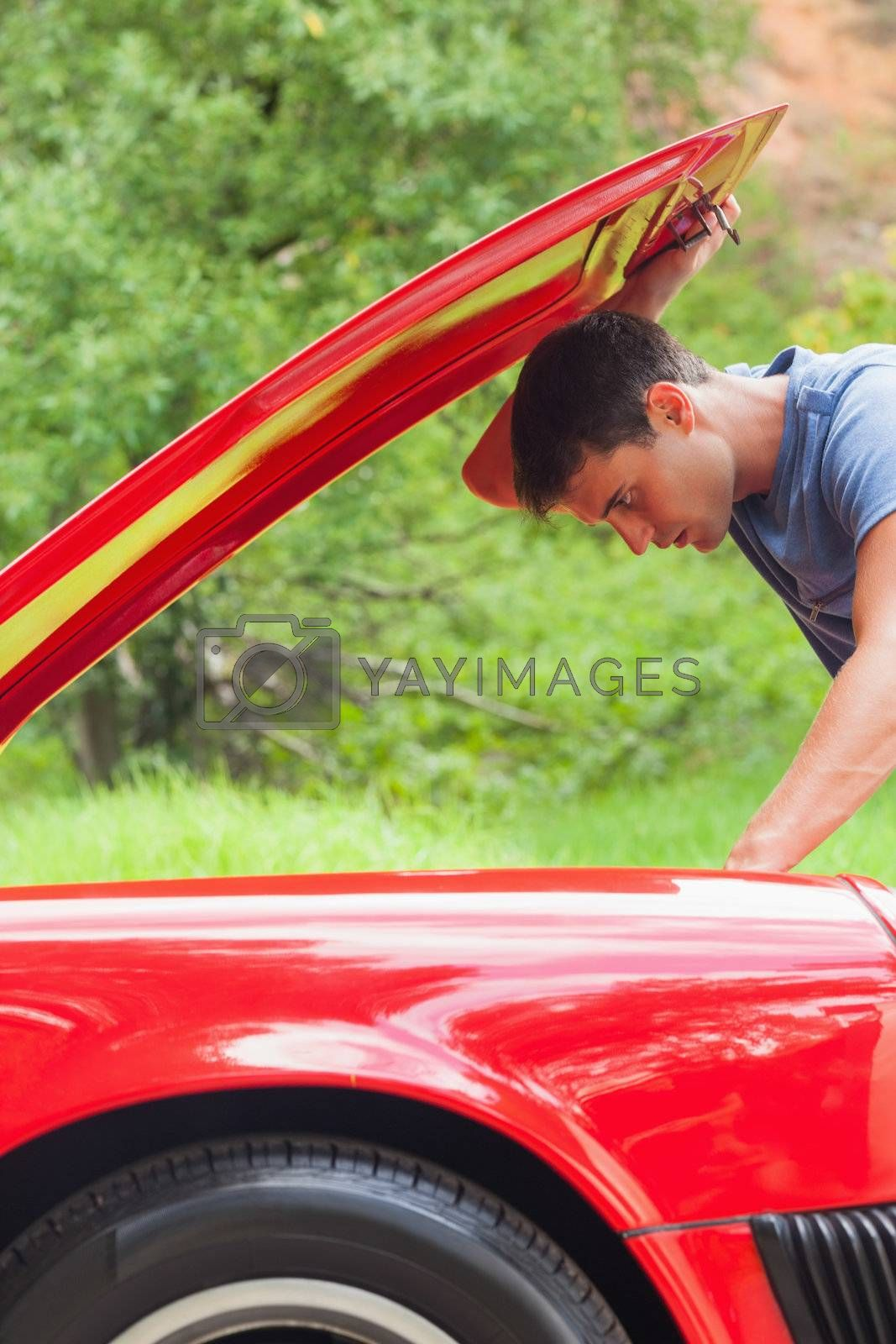 Handsome man checking his car engine by Wavebreakmedia