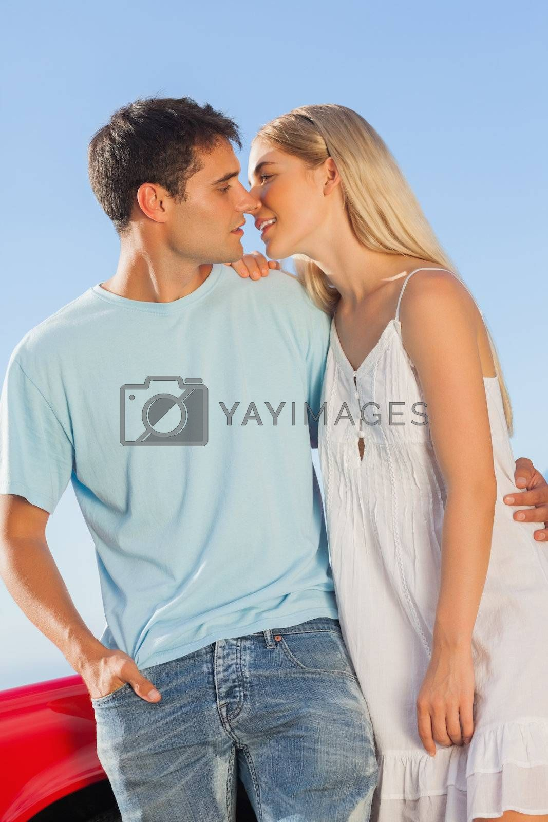 Cute couple against their red cabriolet kissing by Wavebreakmedia