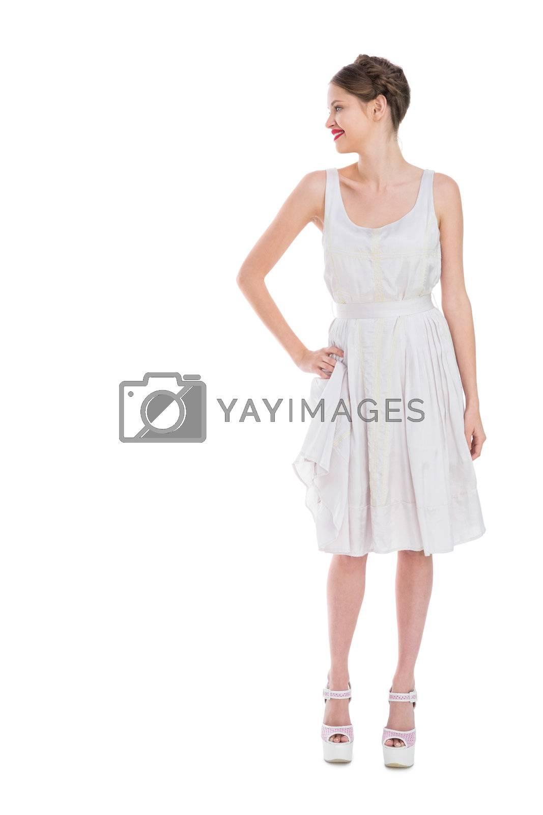 Cheerful pretty woman in white dress posing by Wavebreakmedia