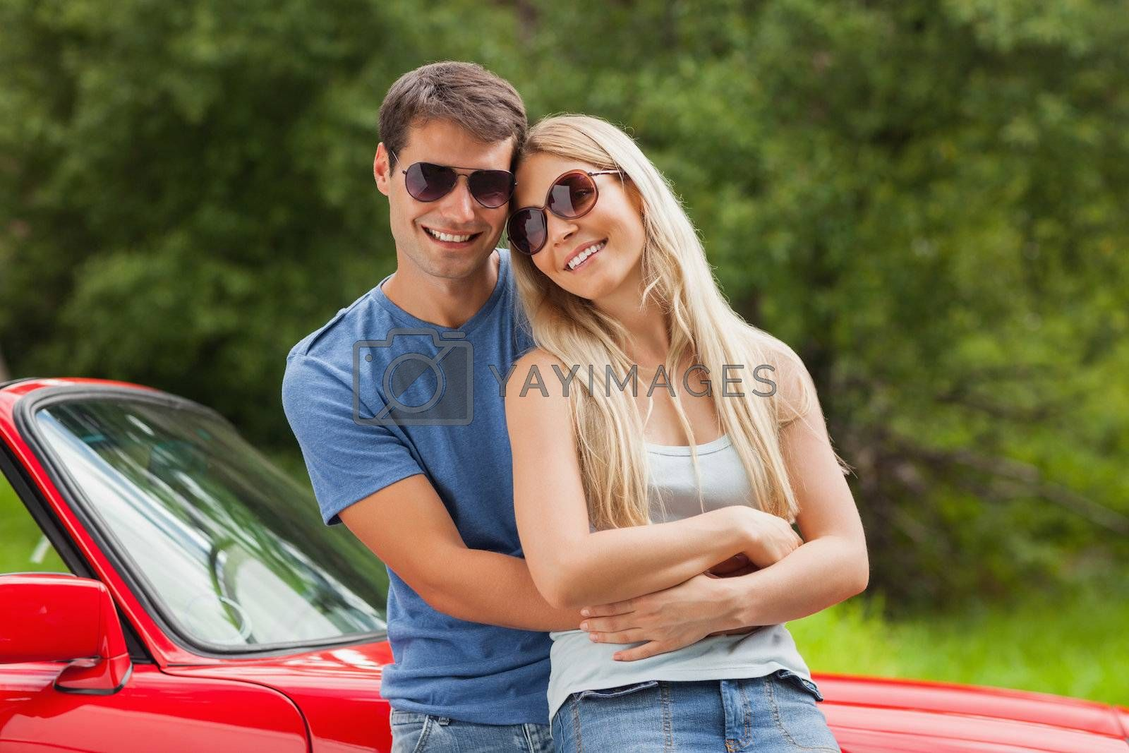 Cheerful couple hugging and leaning against cabriolet by Wavebreakmedia