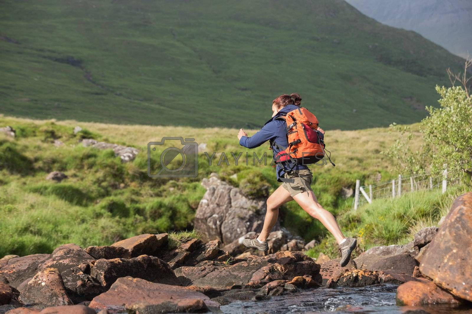 Athletic hiker leaping across rocks in a river by Wavebreakmedia