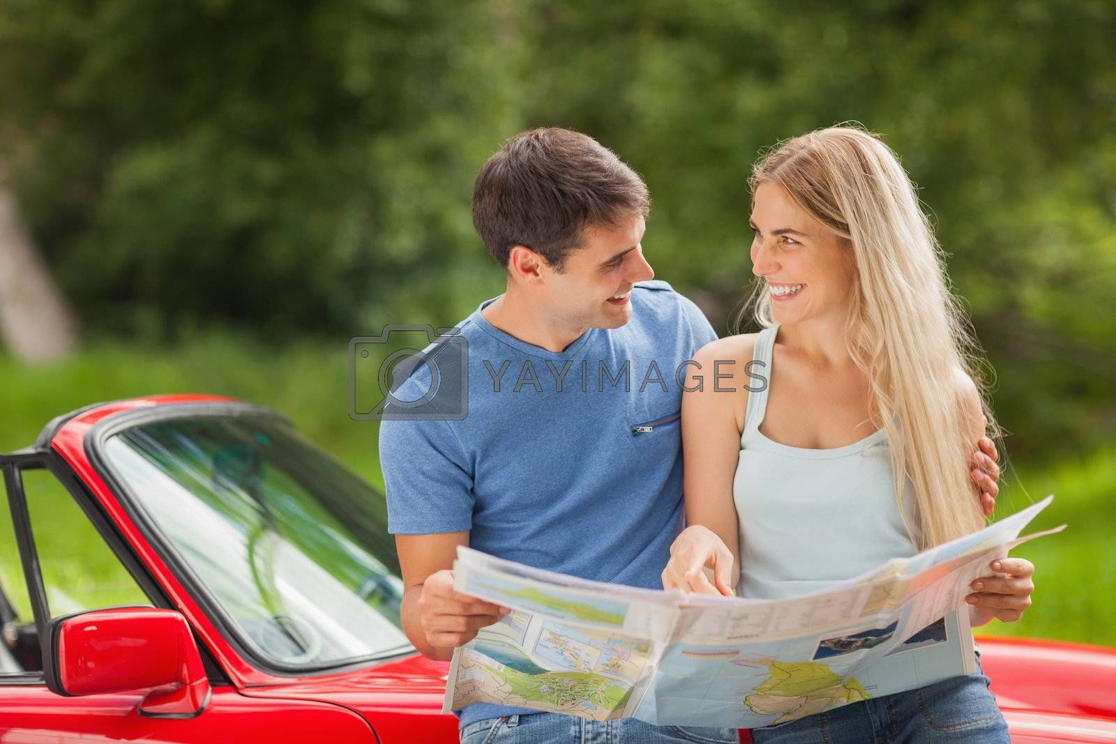 Happy young couple reading map by Wavebreakmedia