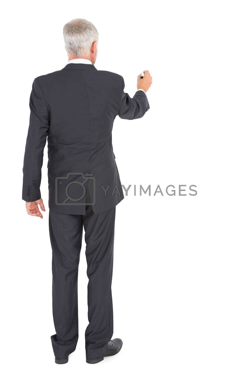 Rear view of businessman standing and writing by Wavebreakmedia