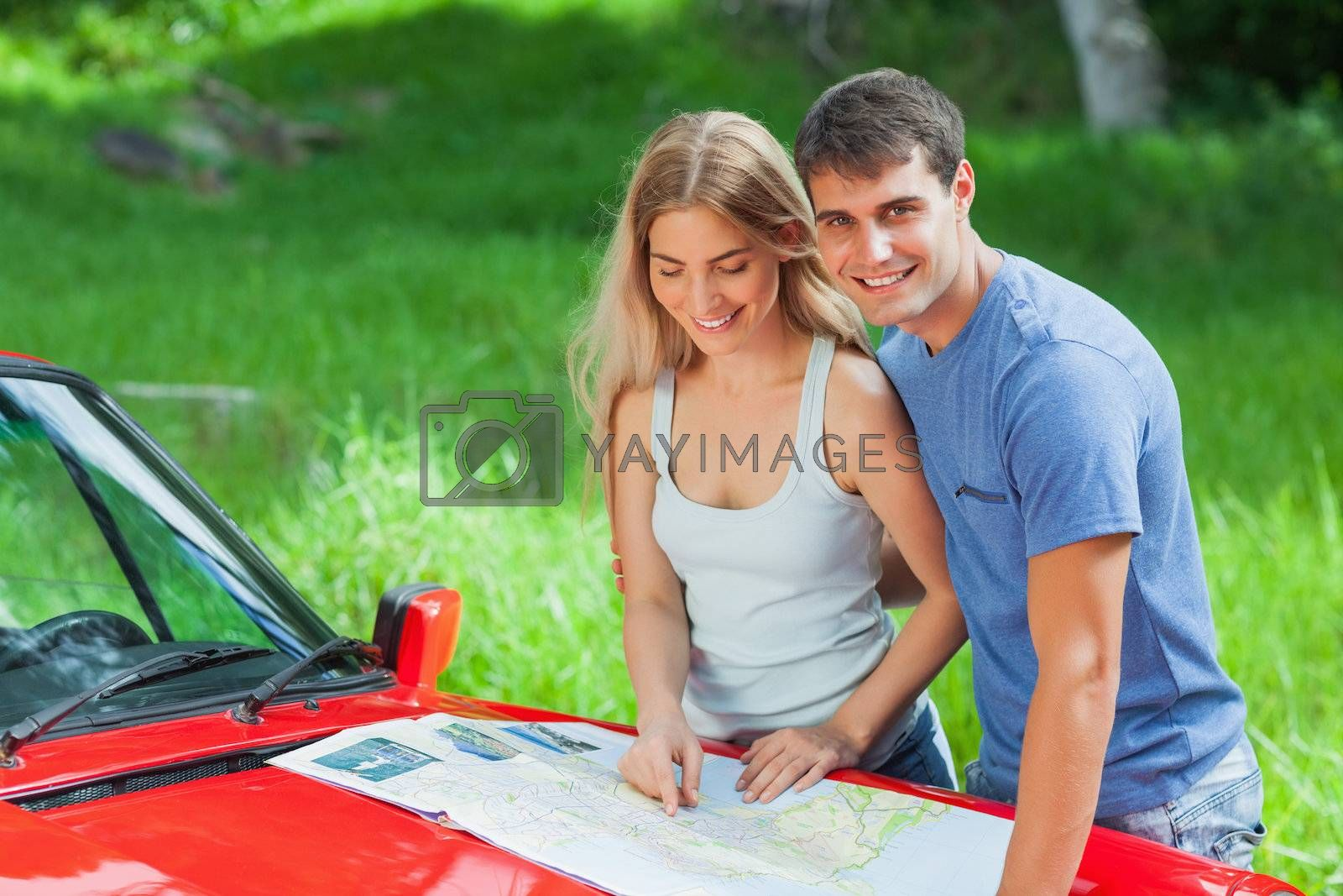 Cheerful young couple reading map on their cabriolet bonnet by Wavebreakmedia