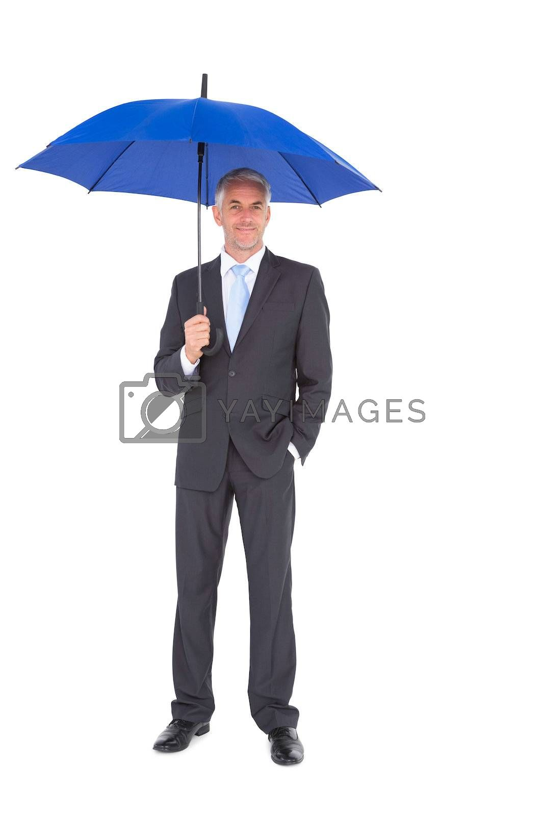 Businessman smiling at camera and holding blue umbrella by Wavebreakmedia