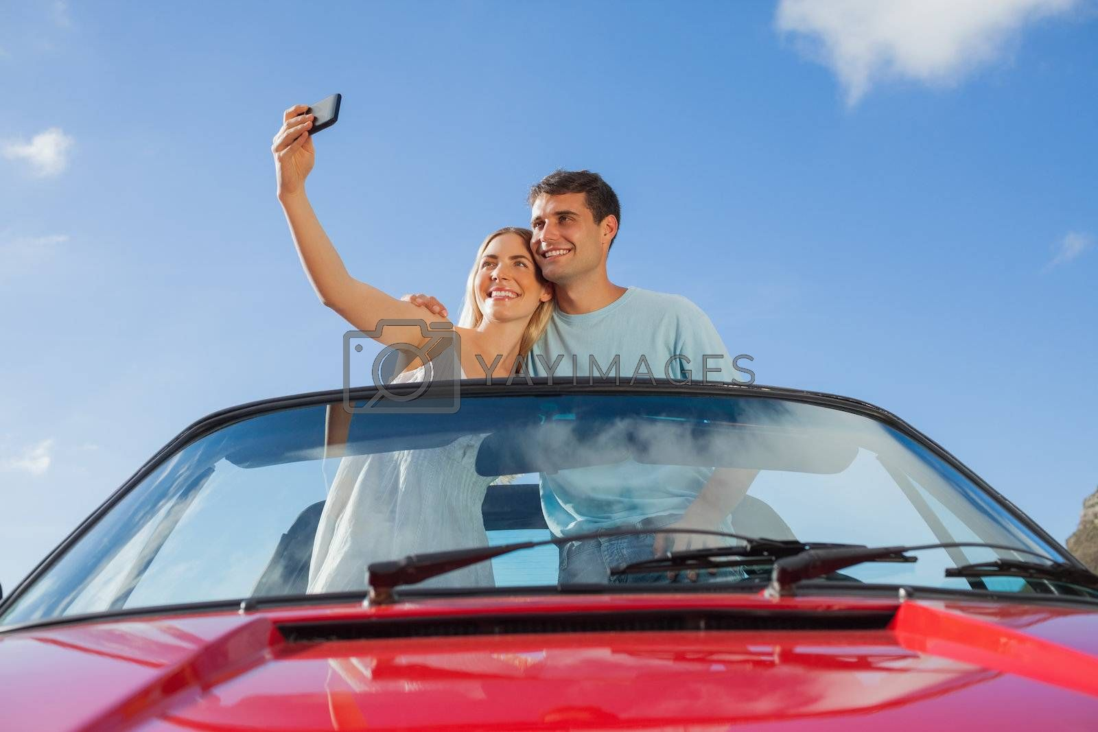 Cheerful couple standing in red cabriolet taking picture by Wavebreakmedia