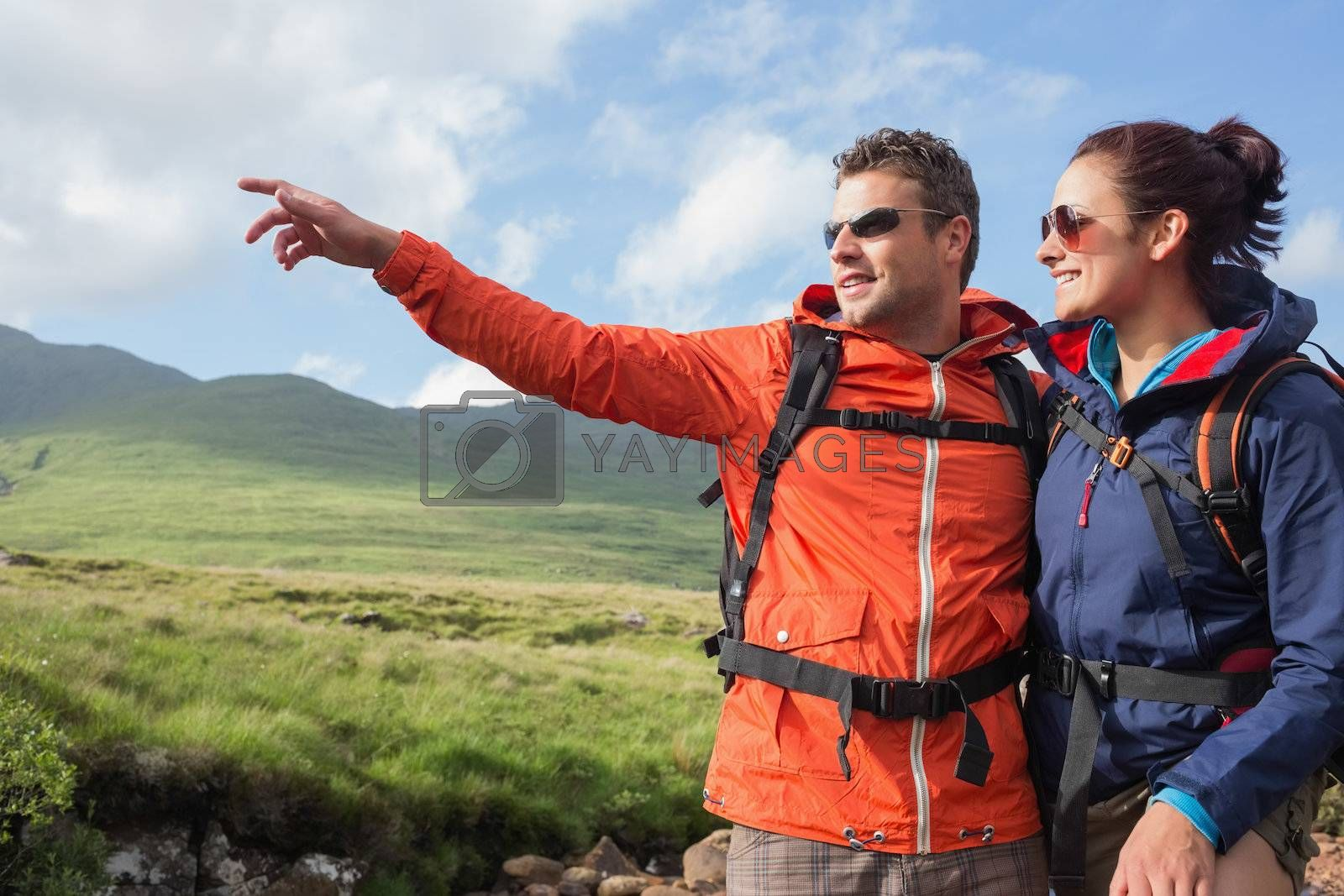 Couple wearing rain jackets and sunglasses admiring the scenery with man pointing by Wavebreakmedia