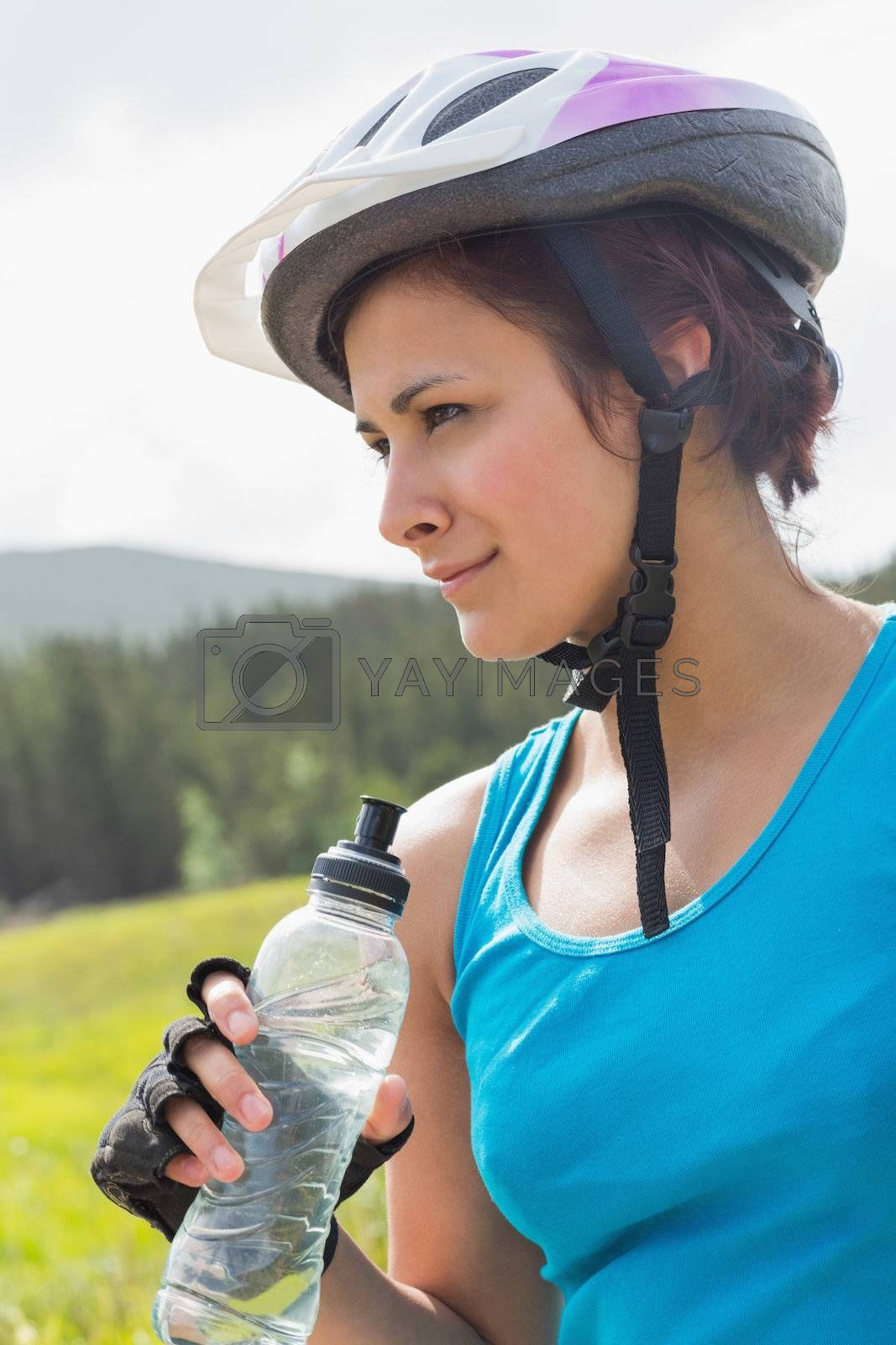 Fit woman wearing bike helmet holding water bottle by Wavebreakmedia