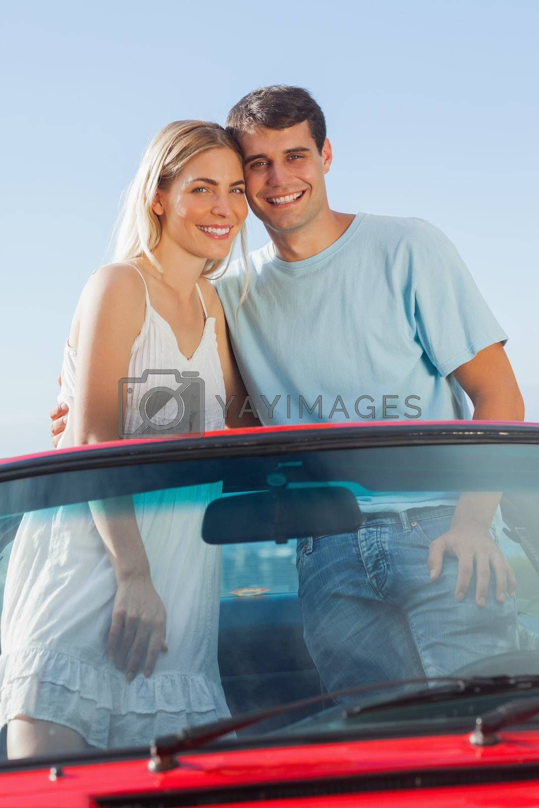 Smiling couple standing in red cabriolet posing by Wavebreakmedia