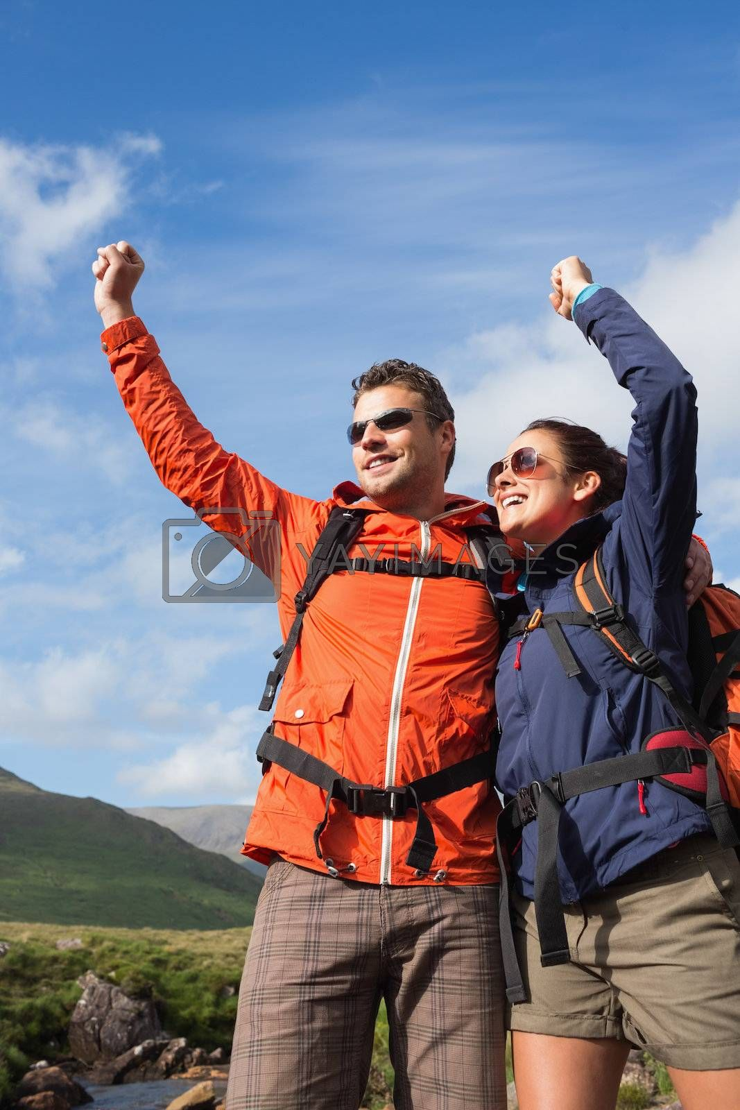 Couple on hike cheering and smiling by Wavebreakmedia