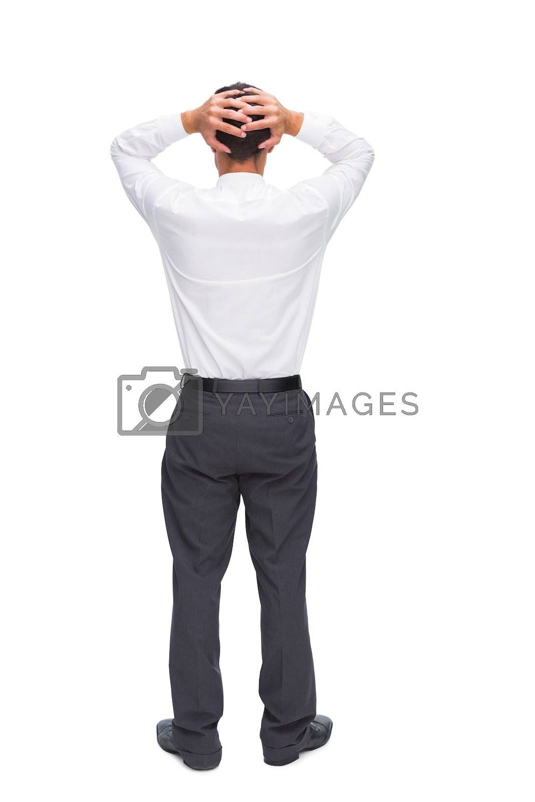 Businessman standing back to camera hands on head by Wavebreakmedia