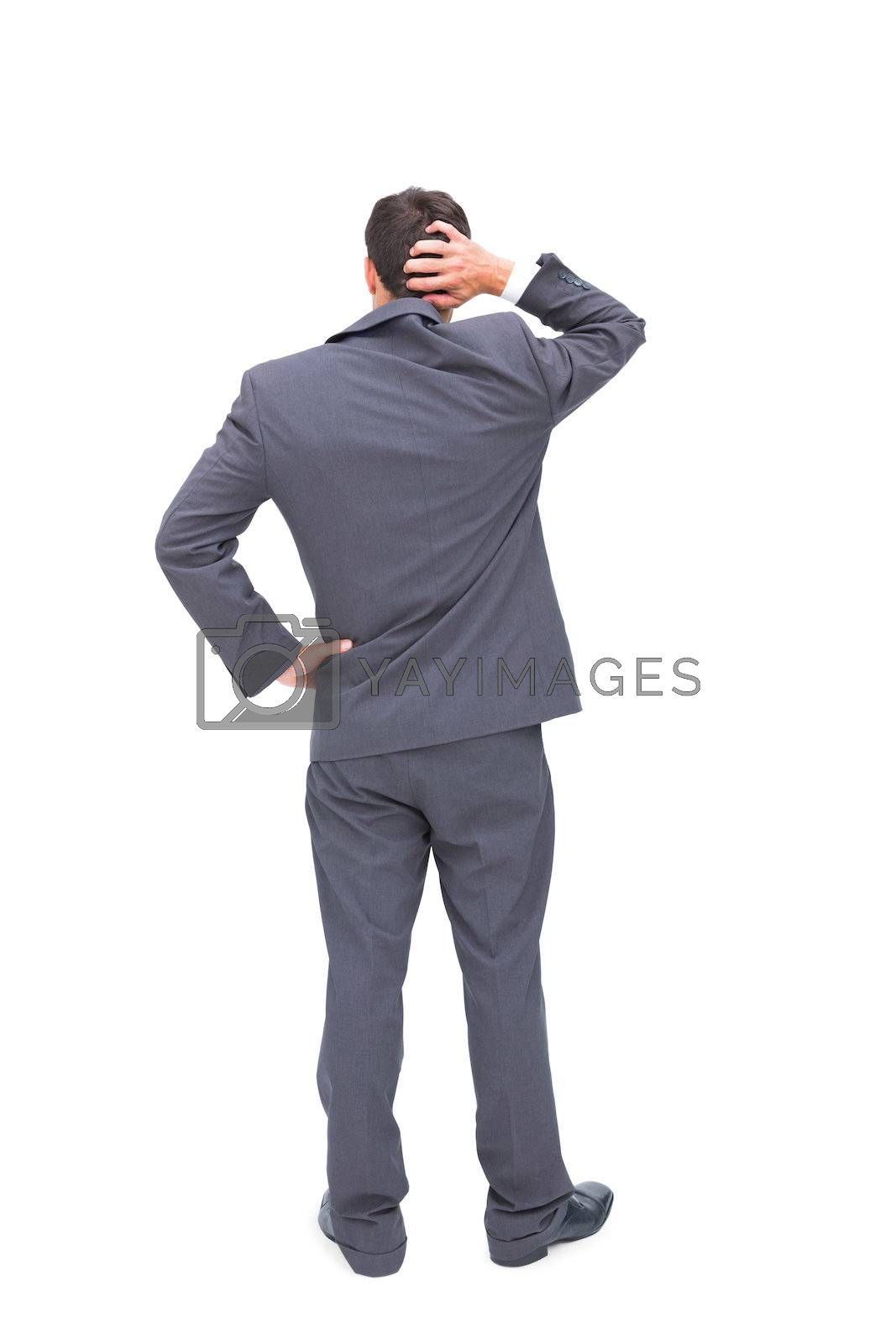 Young businessman standing back to camera scratching his head by Wavebreakmedia