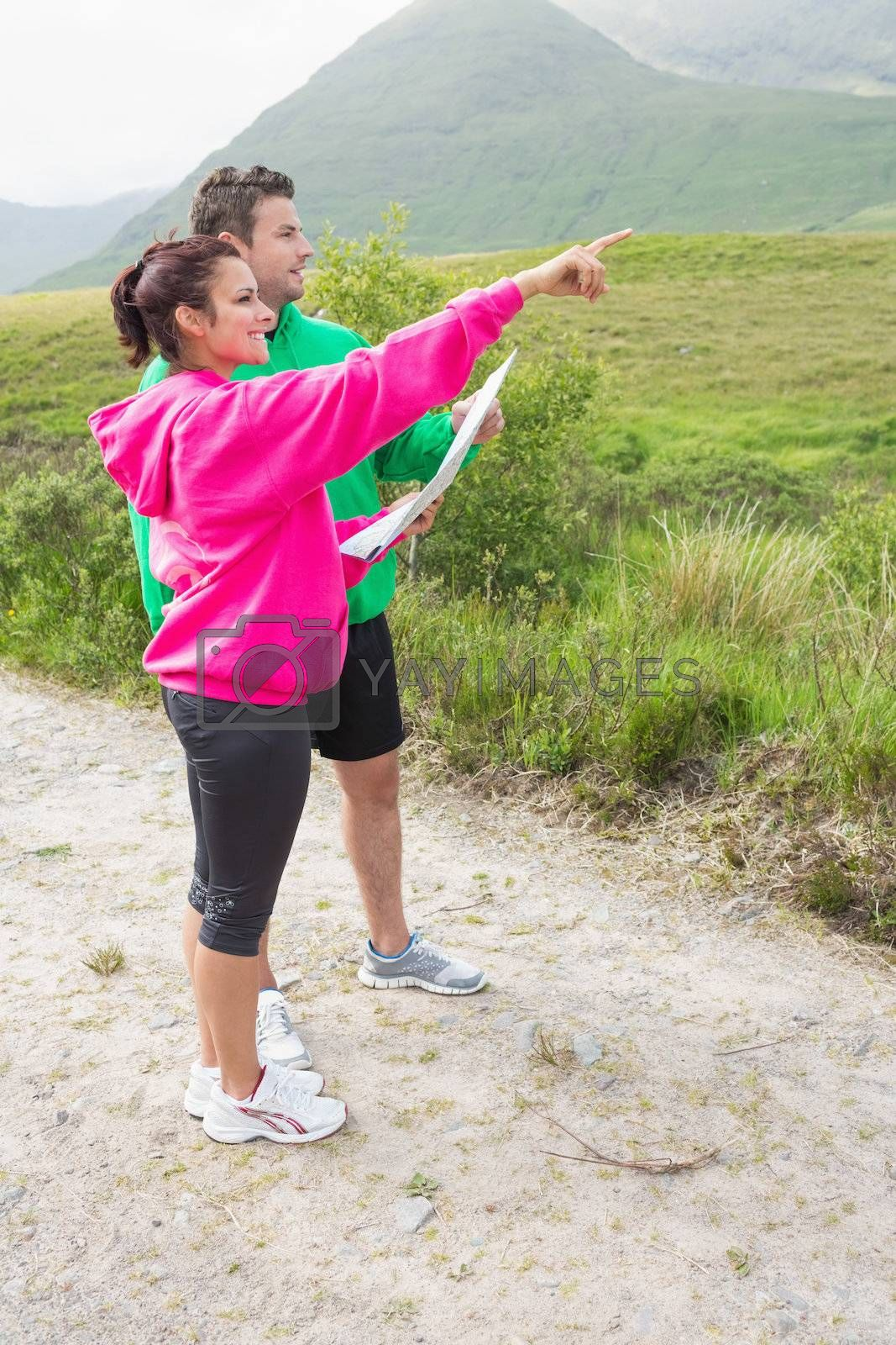 Couple holding a map and pointing ahead by Wavebreakmedia