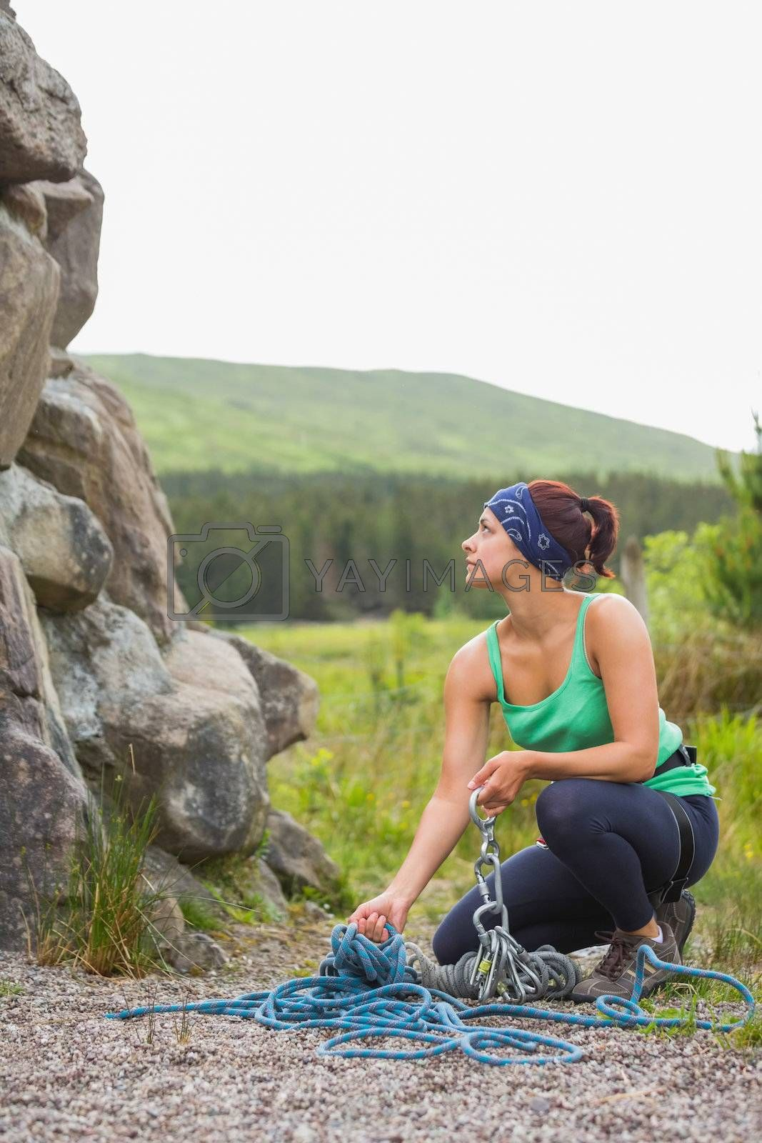Pretty rock climber looking up at her challenge by Wavebreakmedia