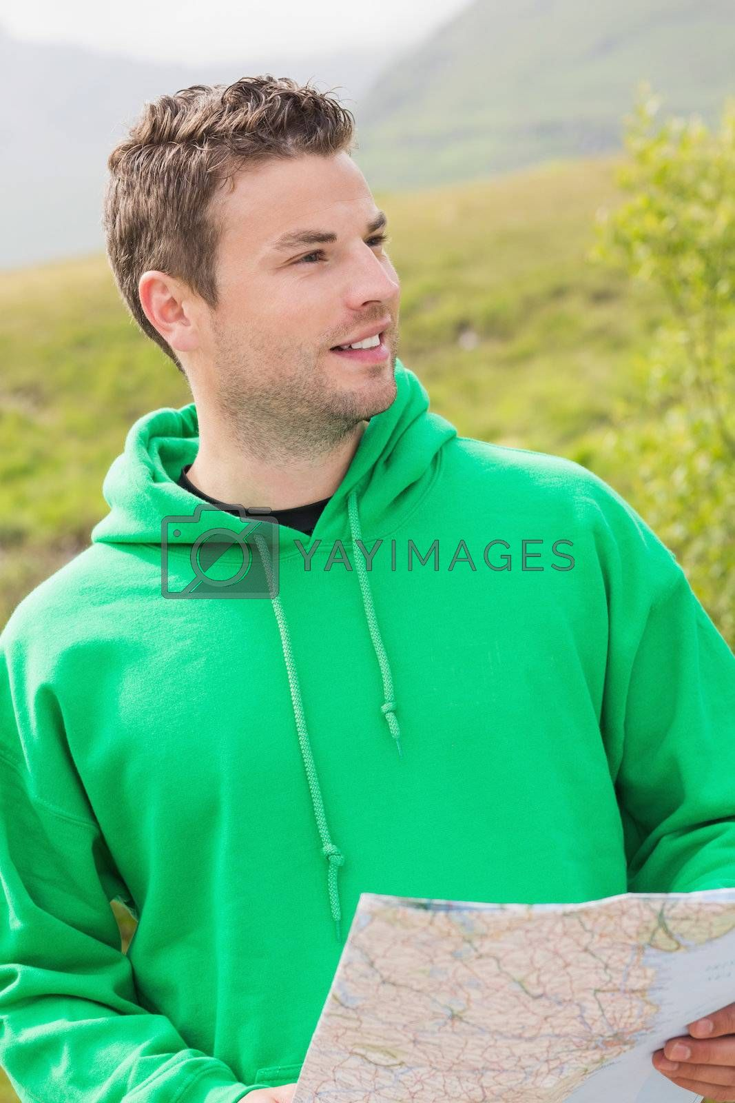 Athletic man holding a map and looking ahead by Wavebreakmedia