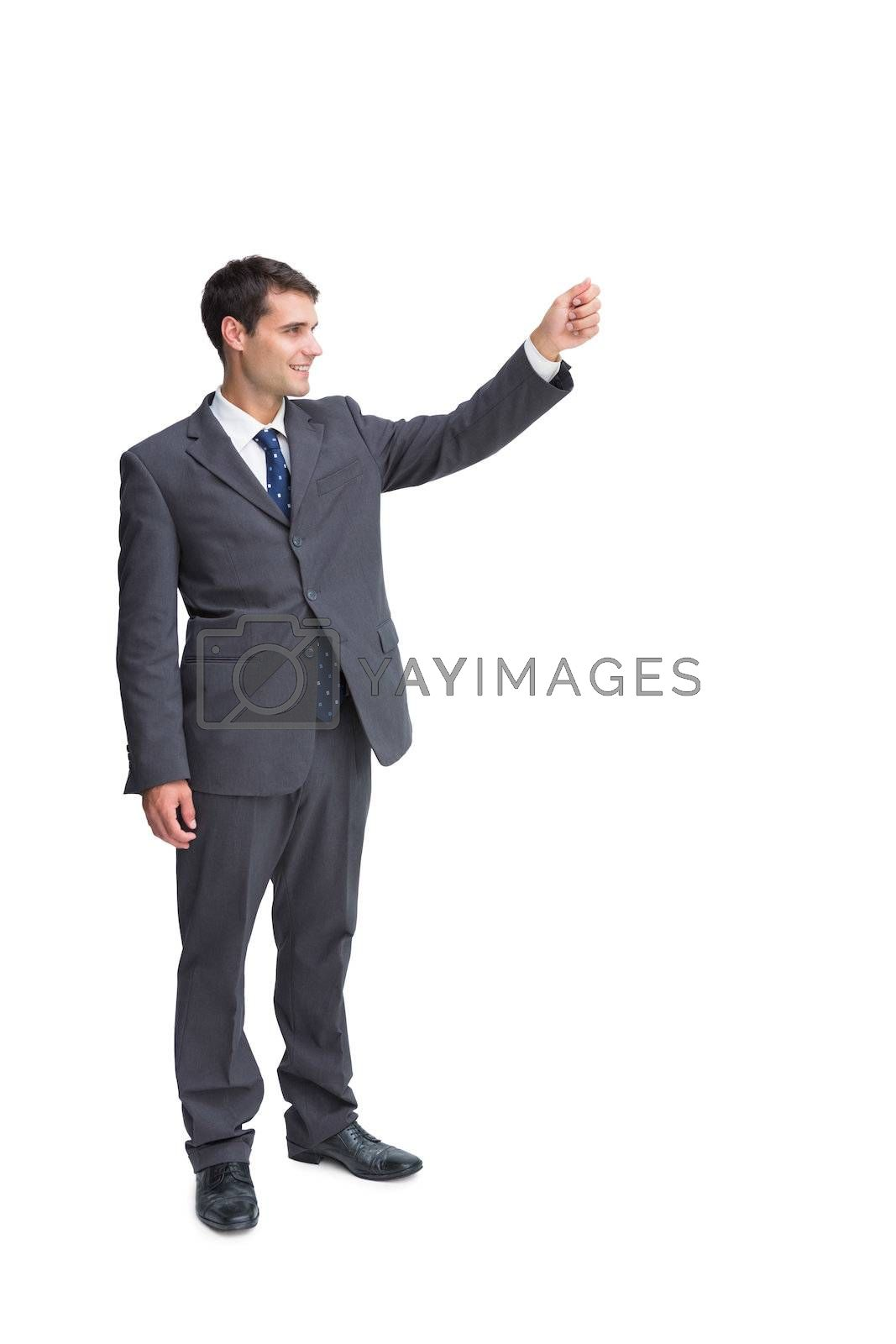 Smiling businessman holding something up in the air by Wavebreakmedia