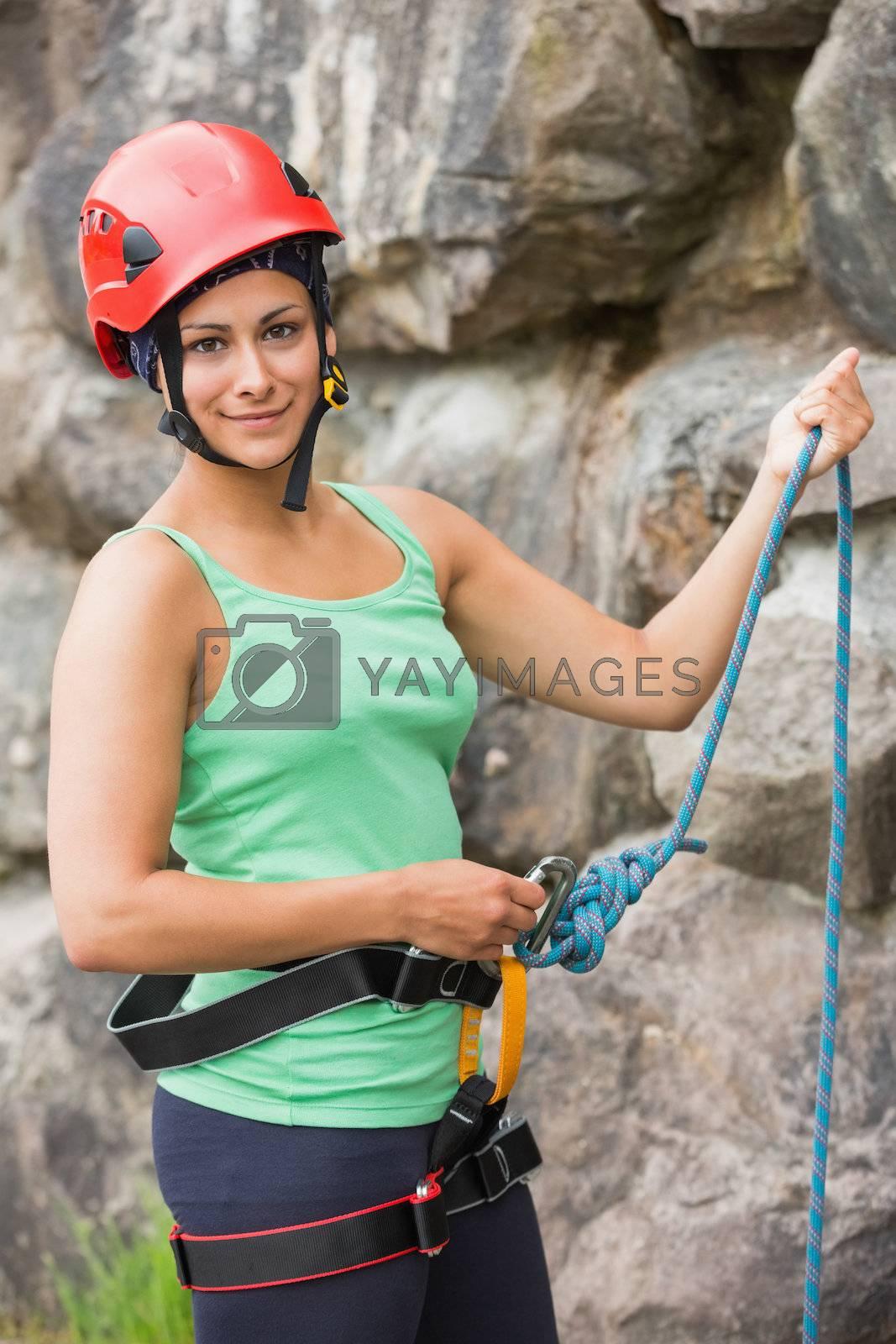 Pretty rock climber about to start her climb by Wavebreakmedia