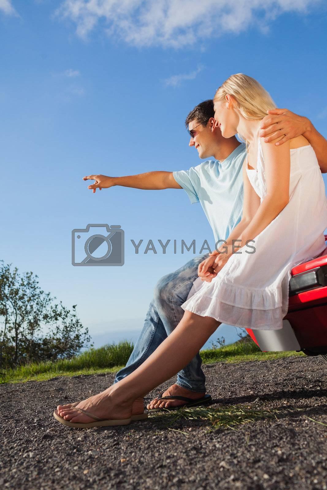 Cheerful cute couple sitting on their cabriolet car hood by Wavebreakmedia