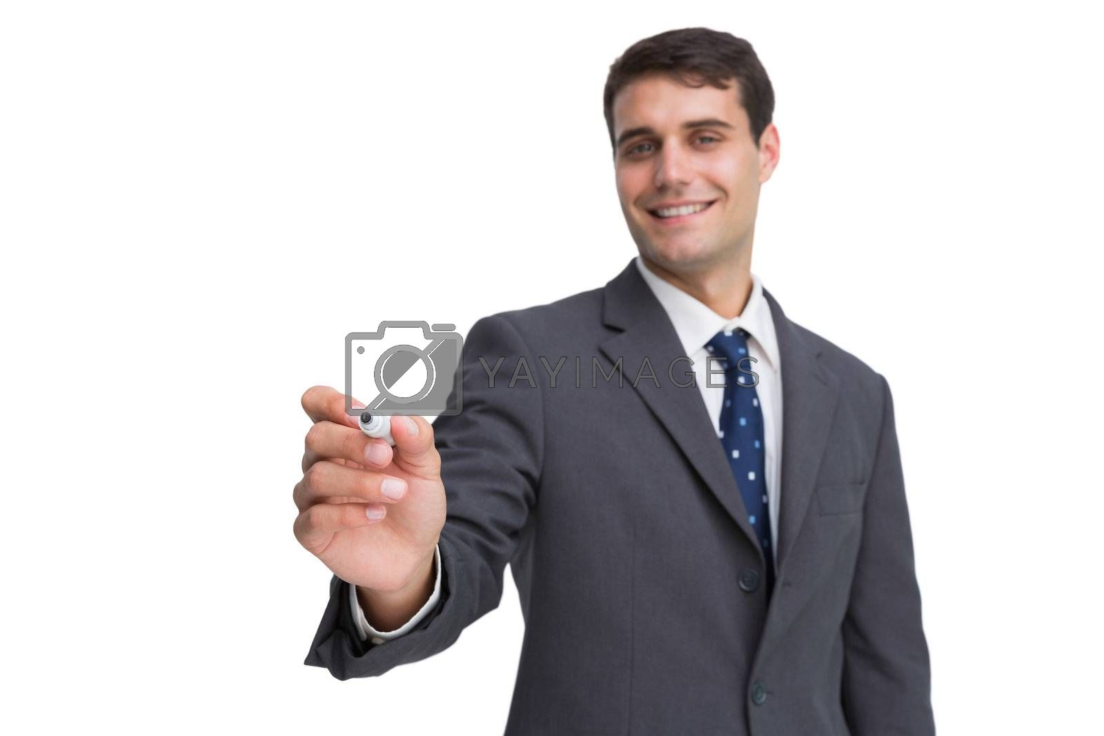 Smiling businessman holding marker and looking at camera by Wavebreakmedia
