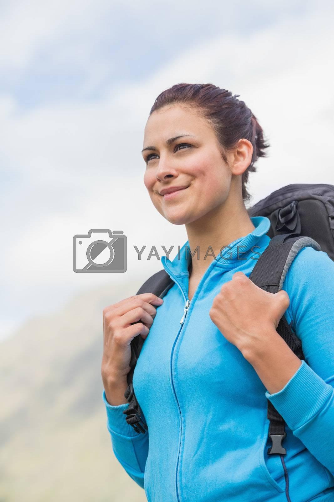 Smiling female hiker with backpack  by Wavebreakmedia