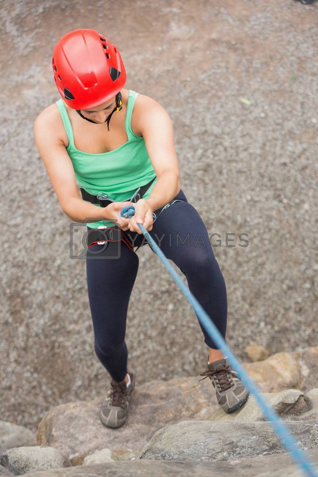 Sporty girl abseiling down rock face by Wavebreakmedia