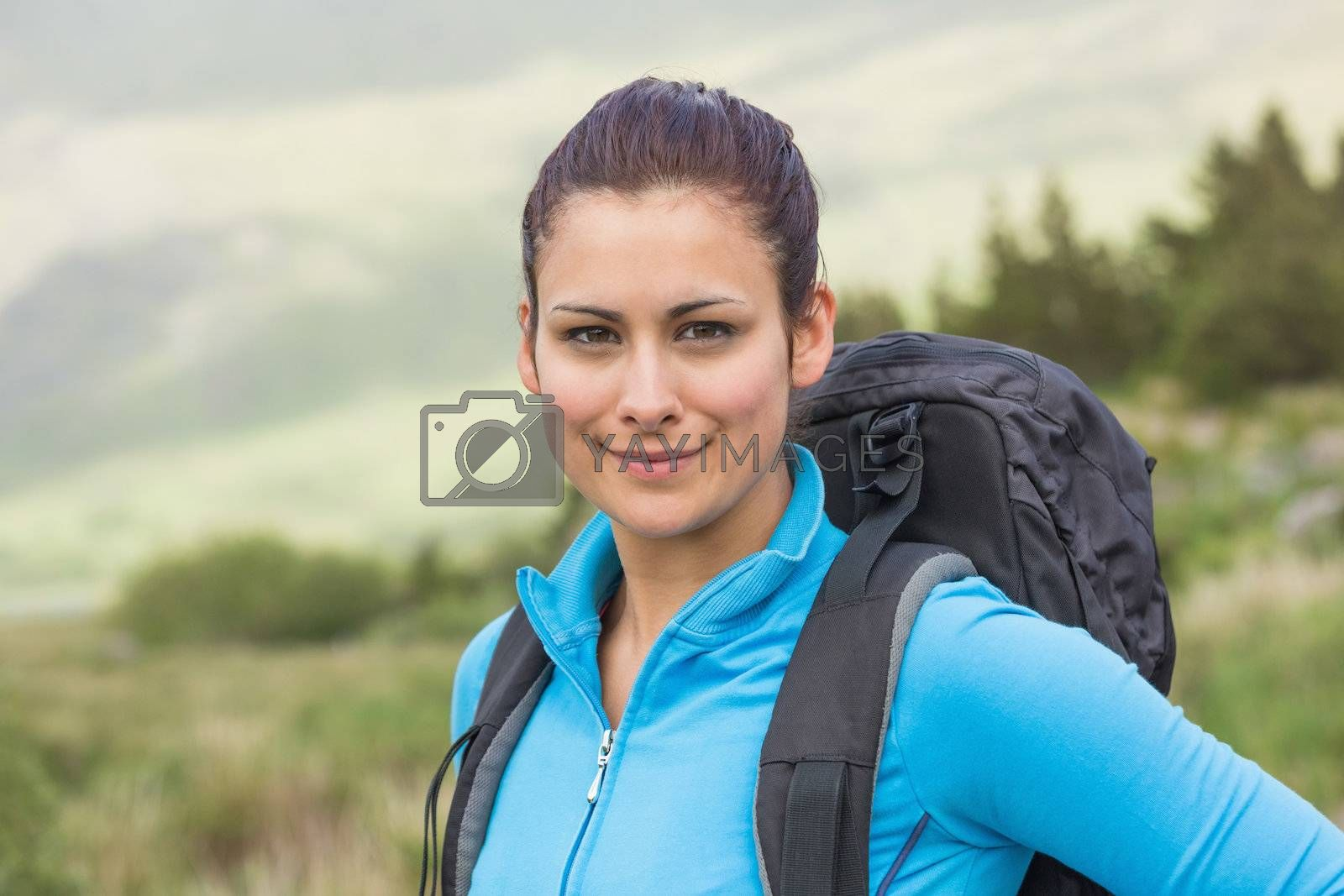 Attractive female hiker with backpack smiling  by Wavebreakmedia