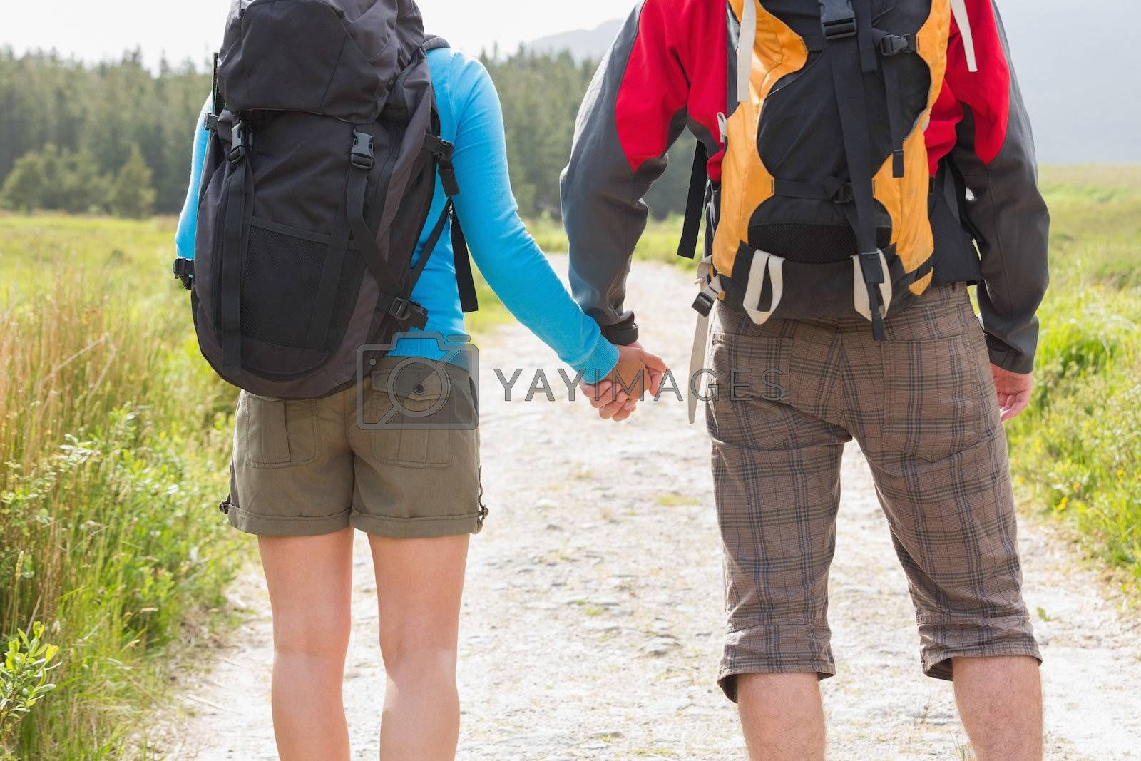 Hikers with backpacks holding hands by Wavebreakmedia