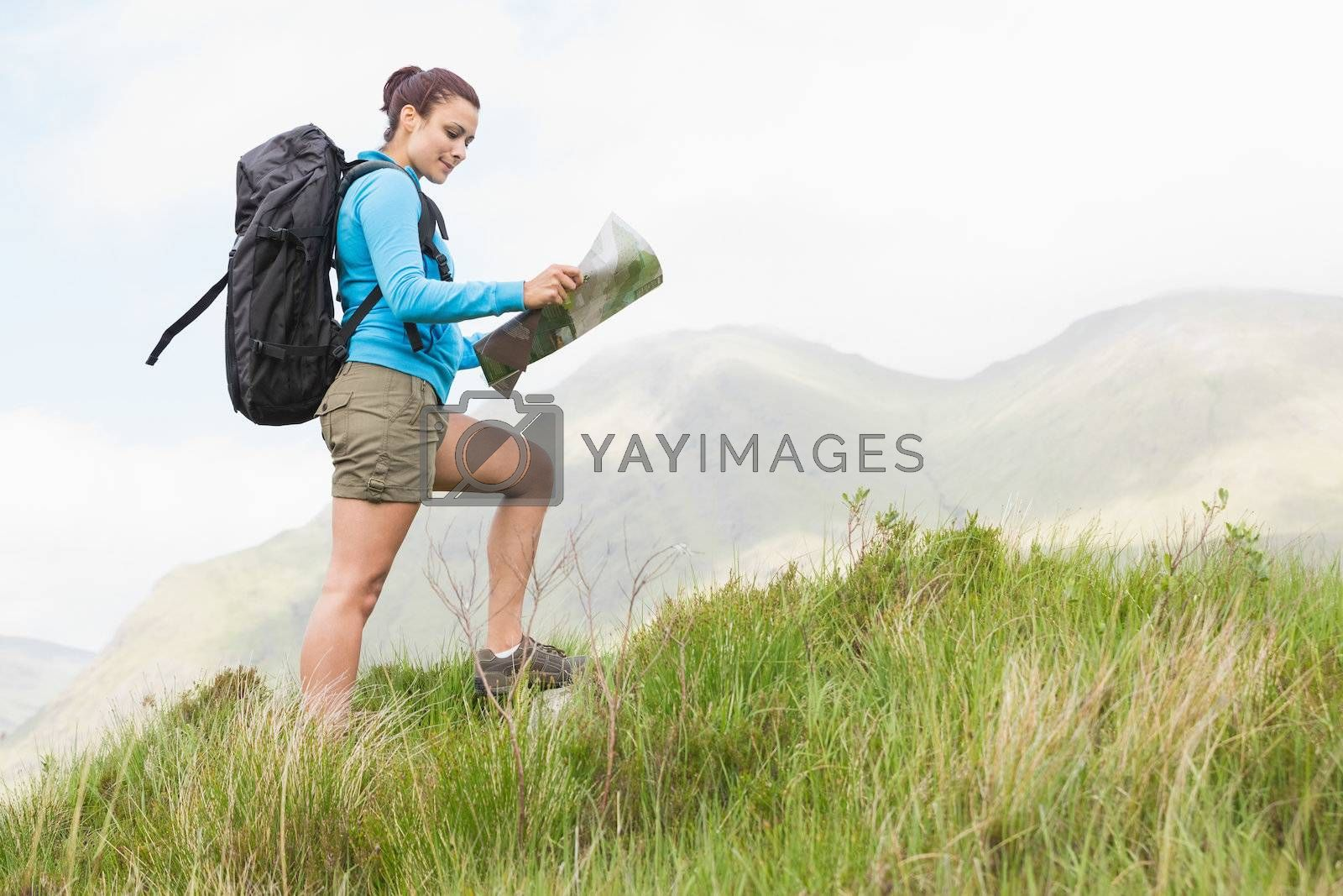 Attractive hiker with backpack walking uphill reading a map by Wavebreakmedia
