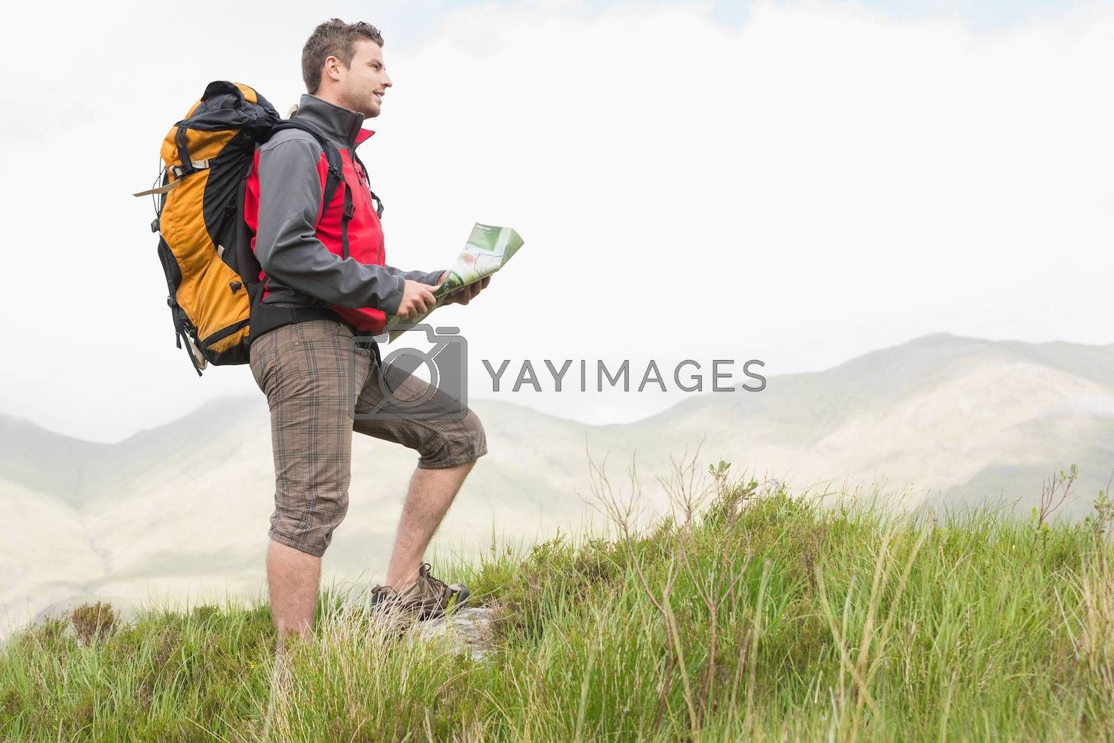 Handsome hiker with backpack hiking uphill holding a map by Wavebreakmedia
