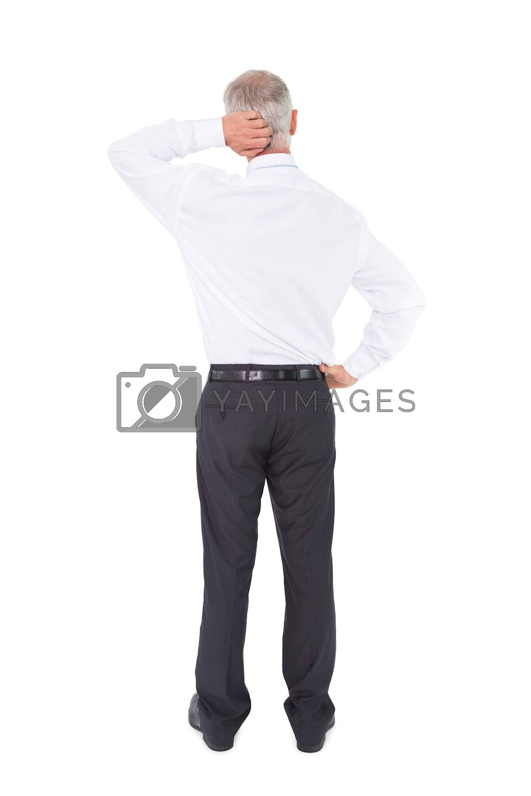Businessman standing back to camera scratching his head by Wavebreakmedia