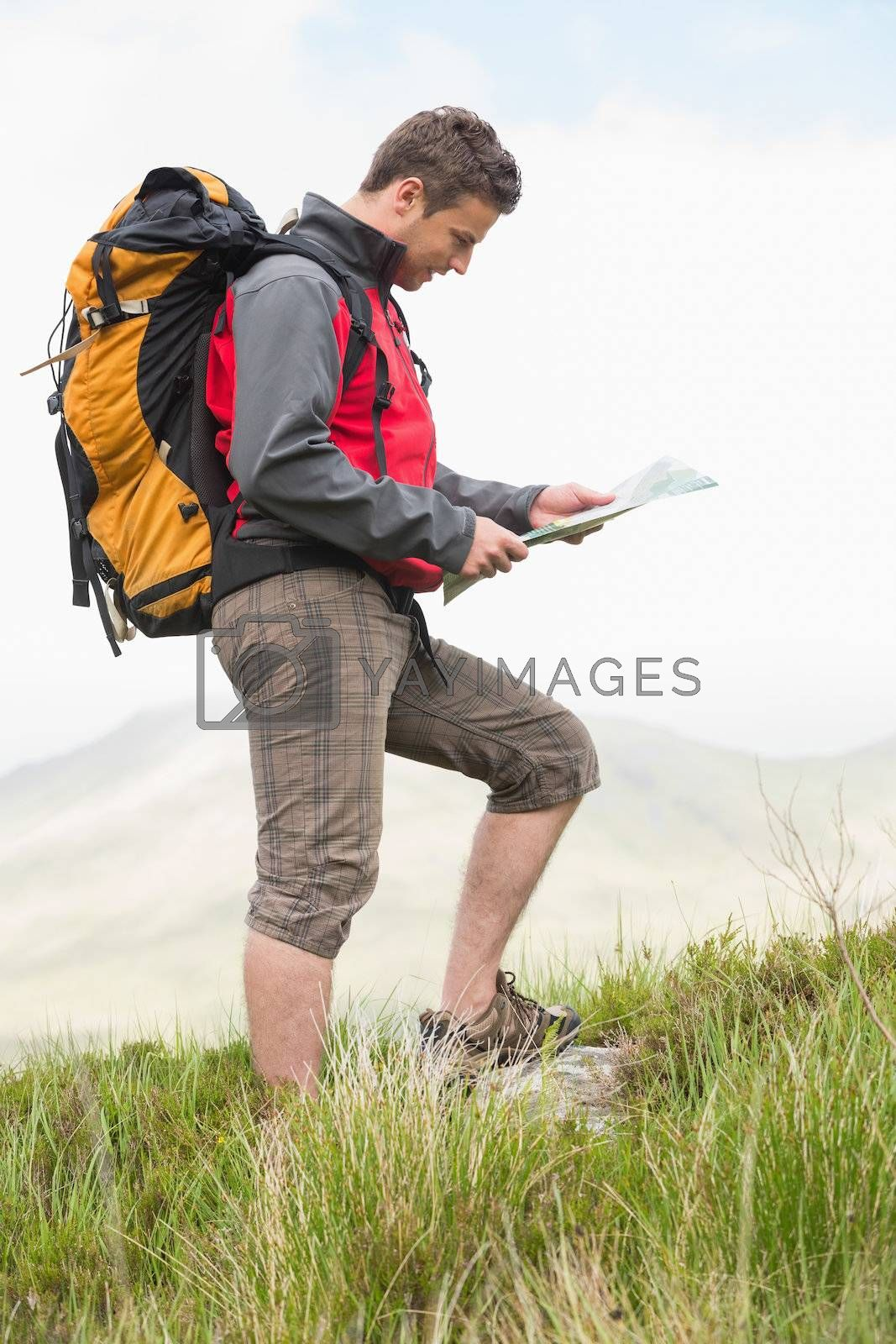 Handsome hiker with backpack walking uphill reading a map by Wavebreakmedia