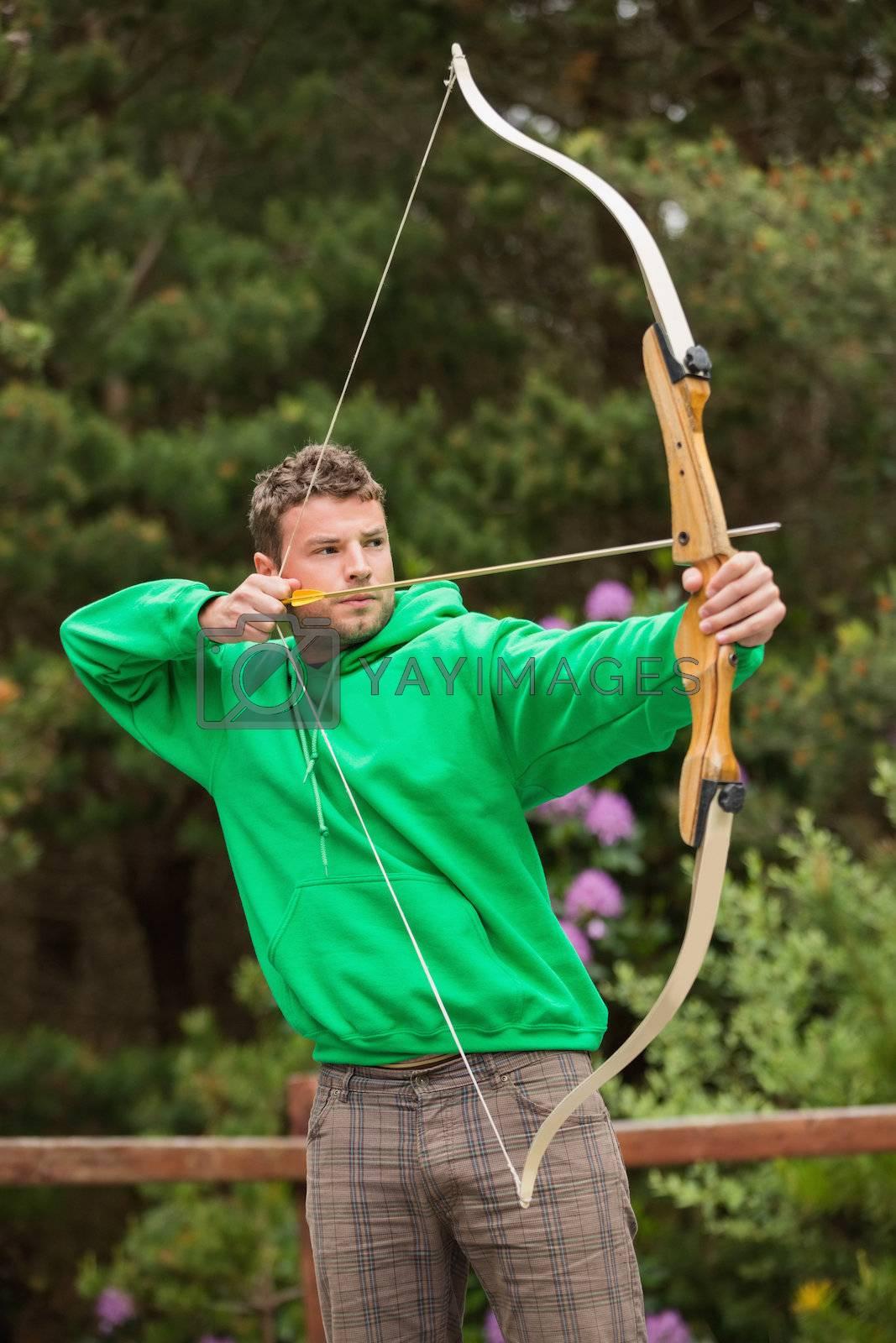 Focused man practicing archery by Wavebreakmedia