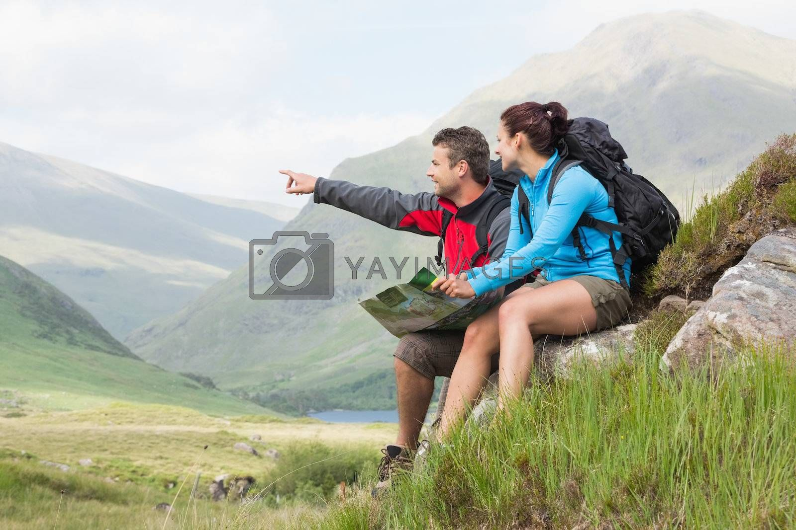 Couple taking a break after hiking uphill and holding map by Wavebreakmedia