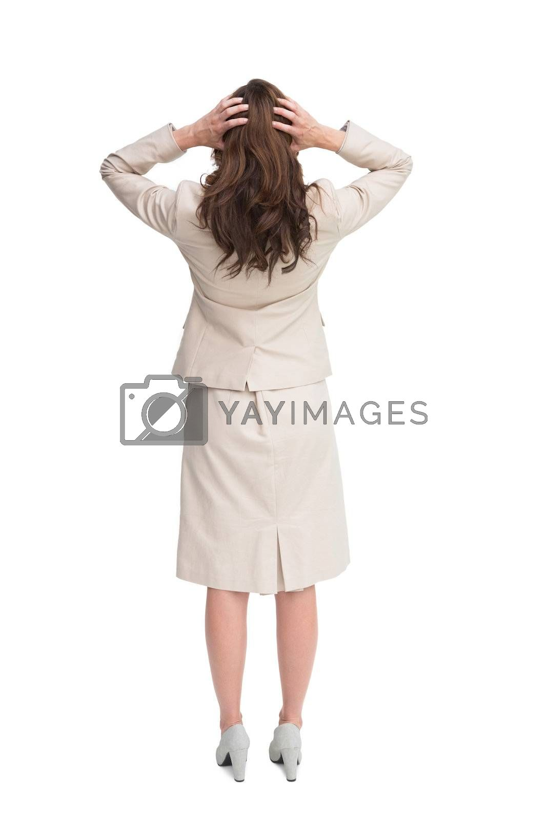 Businesswoman with hands on head standing back to camera by Wavebreakmedia